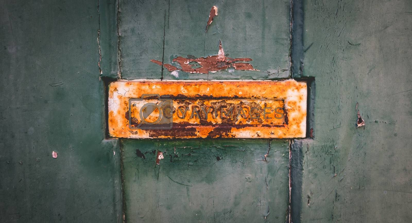 old rusty Portuguese mailbox on a worn wooden door where it is written in Portuguese: mail
