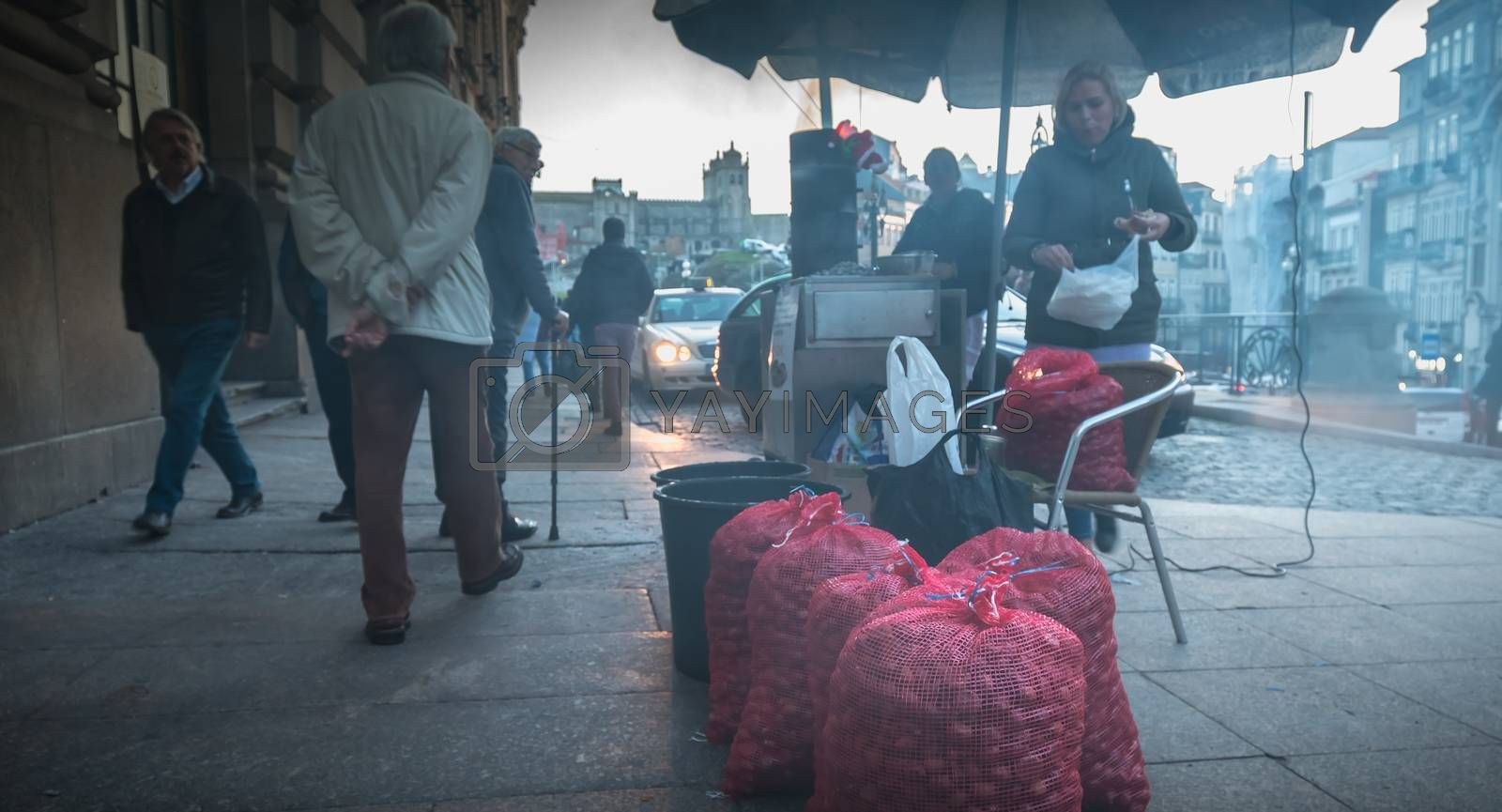 Porto, Portugal - 30 November 2018: Street vendors of roasted chestnuts in front of Sao Bento station in the city center on a fall day