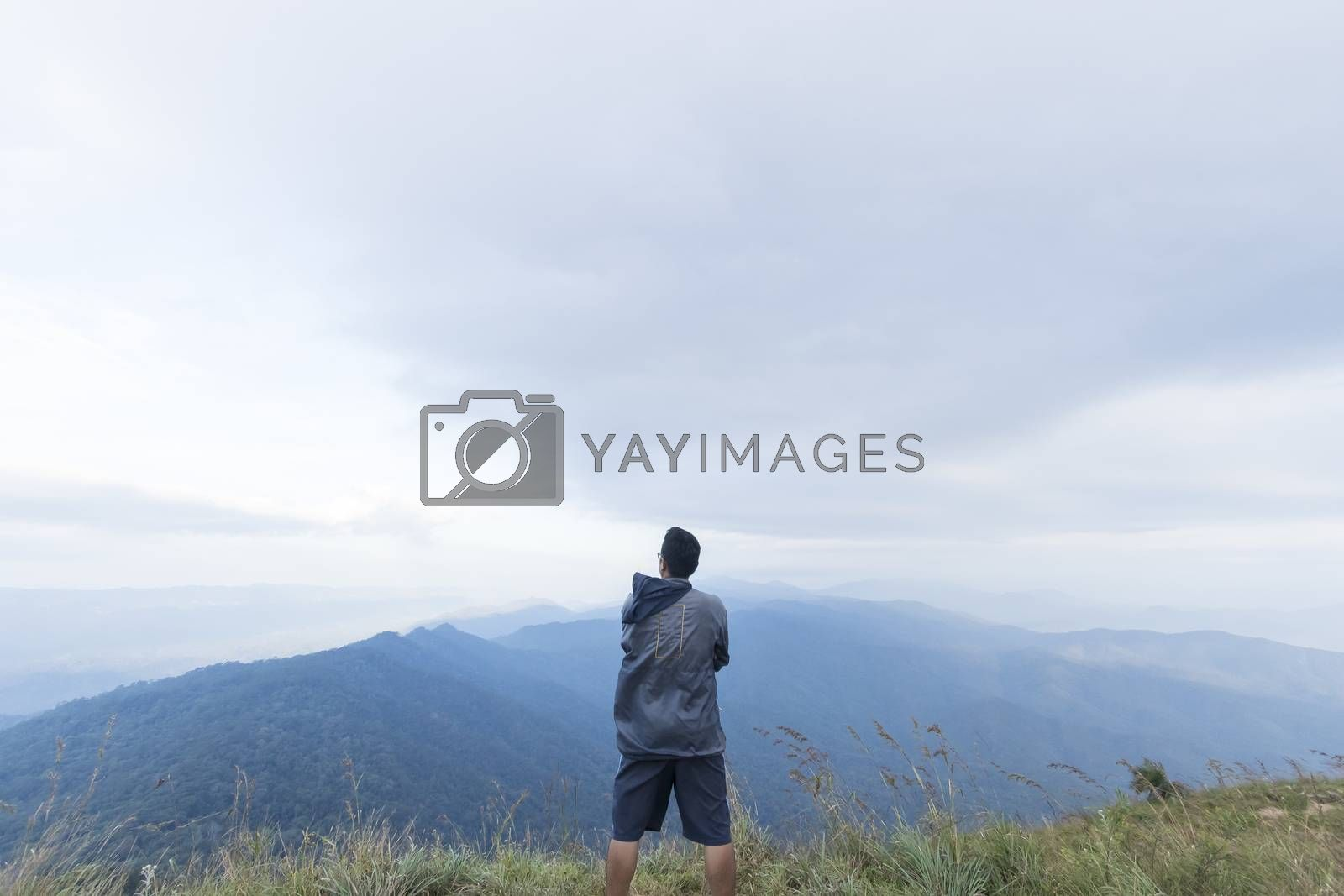 Young man standing on top of mountain