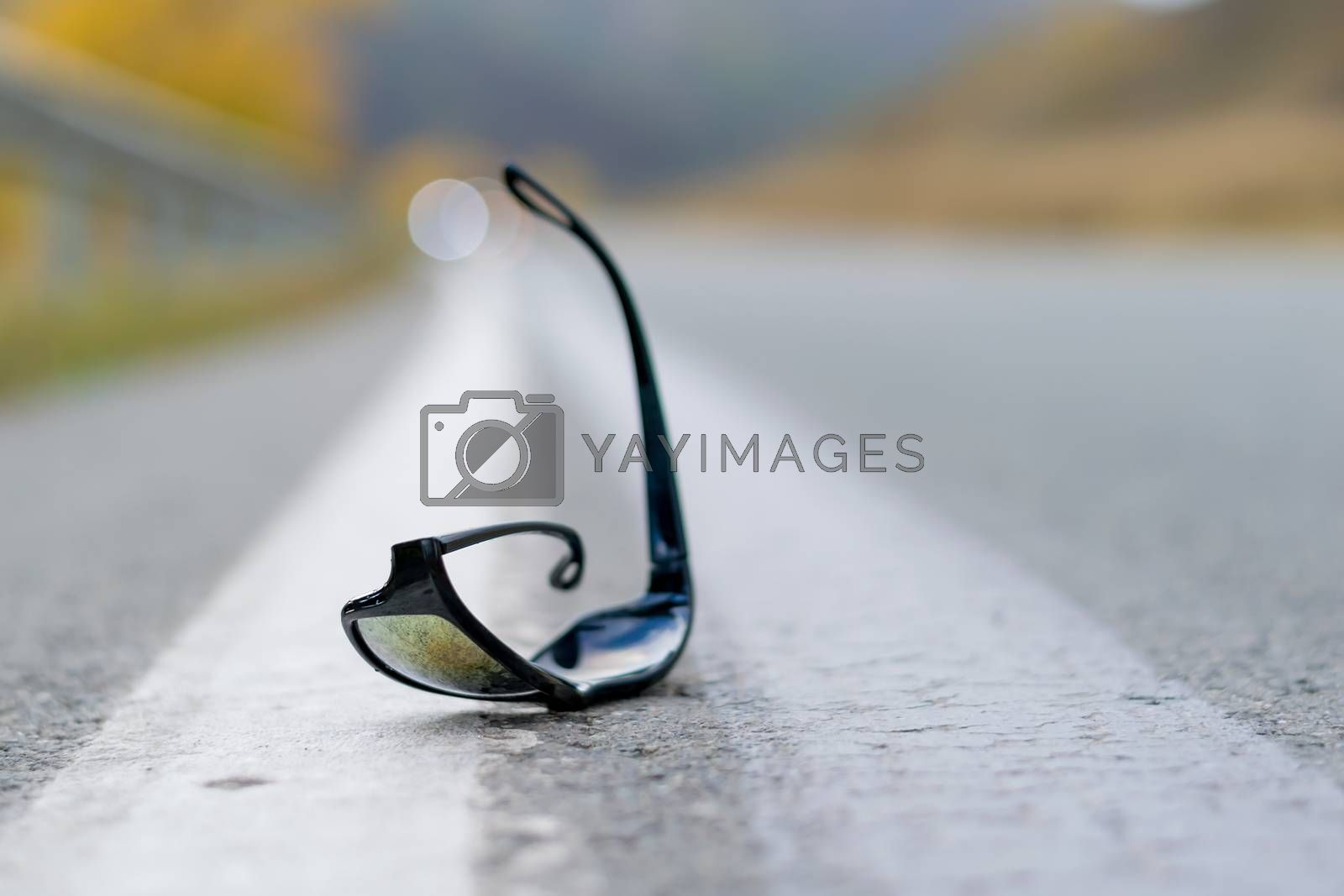 close up, lost sunglasses lie on the road asphalt on a country track on the dividing strip at the curb