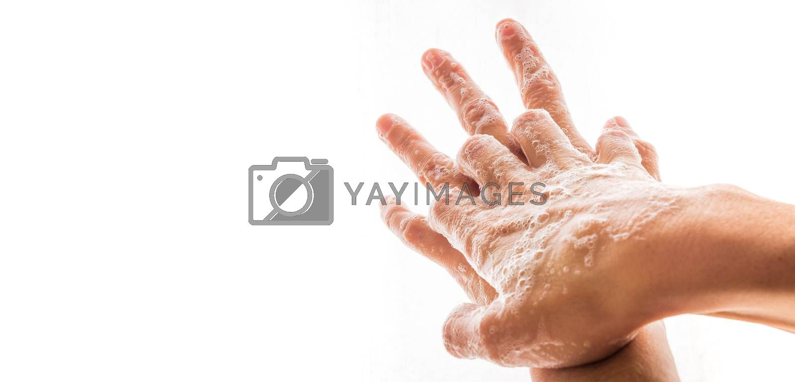 Two human hands washing with soap and bubbles.