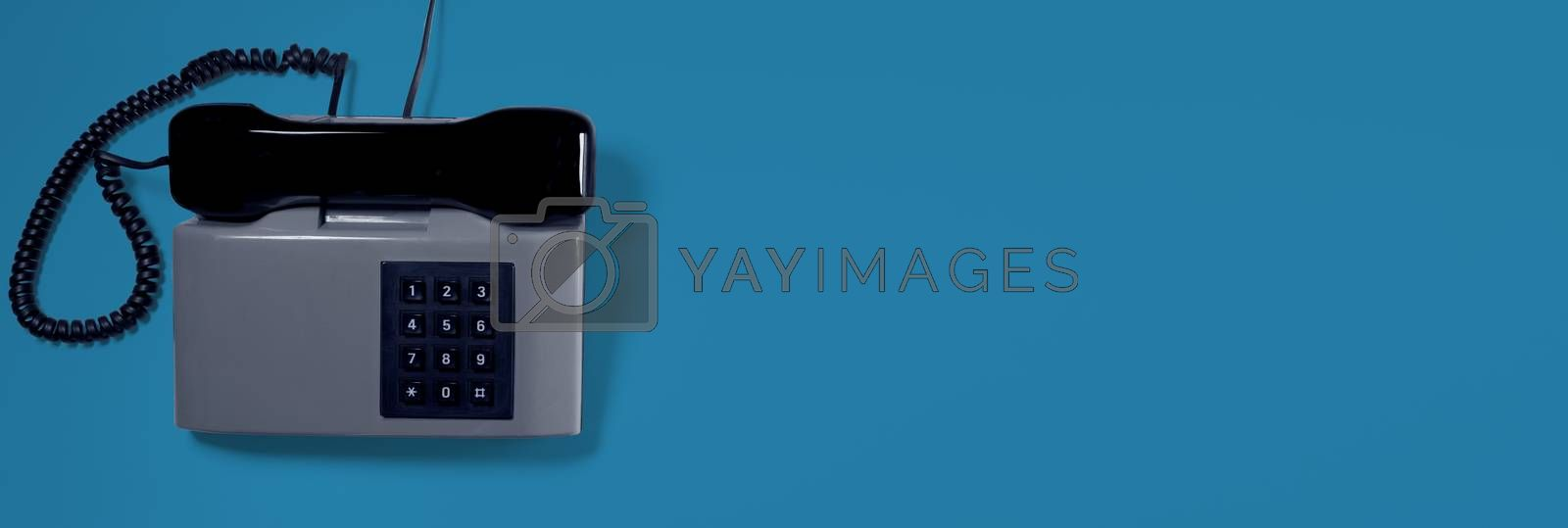 A grey vintage telephone with blue background. Business card.