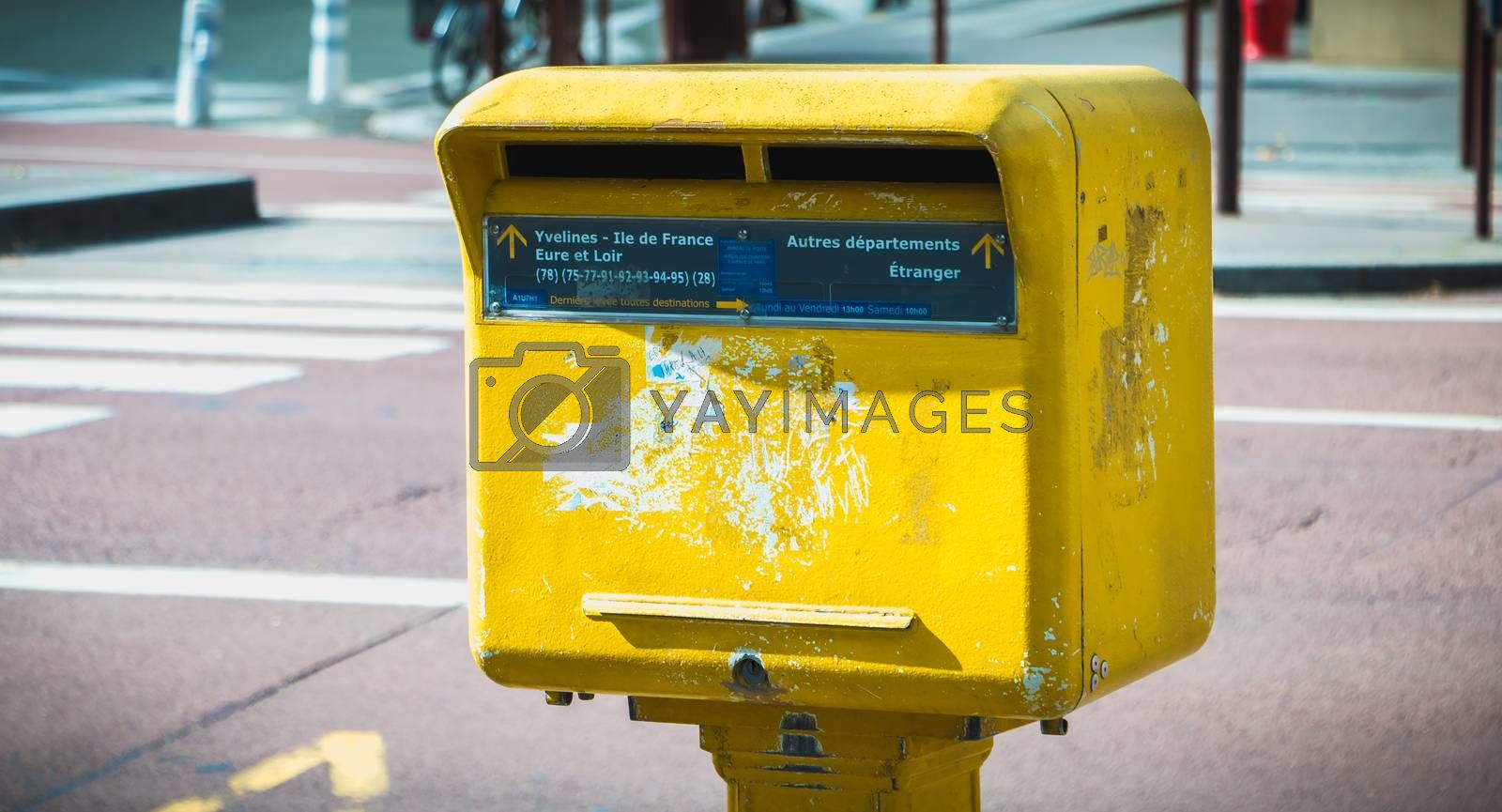 Versailles, France - October 9, 2017: Yellow Post mailbox in the city center on a fall day