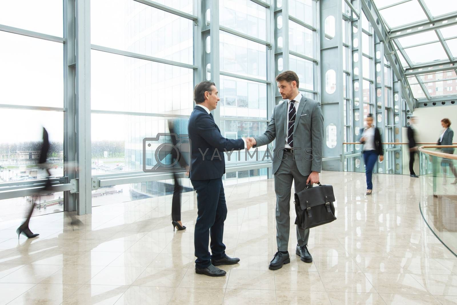 Business people shaking hands standing in a crowd of walking people