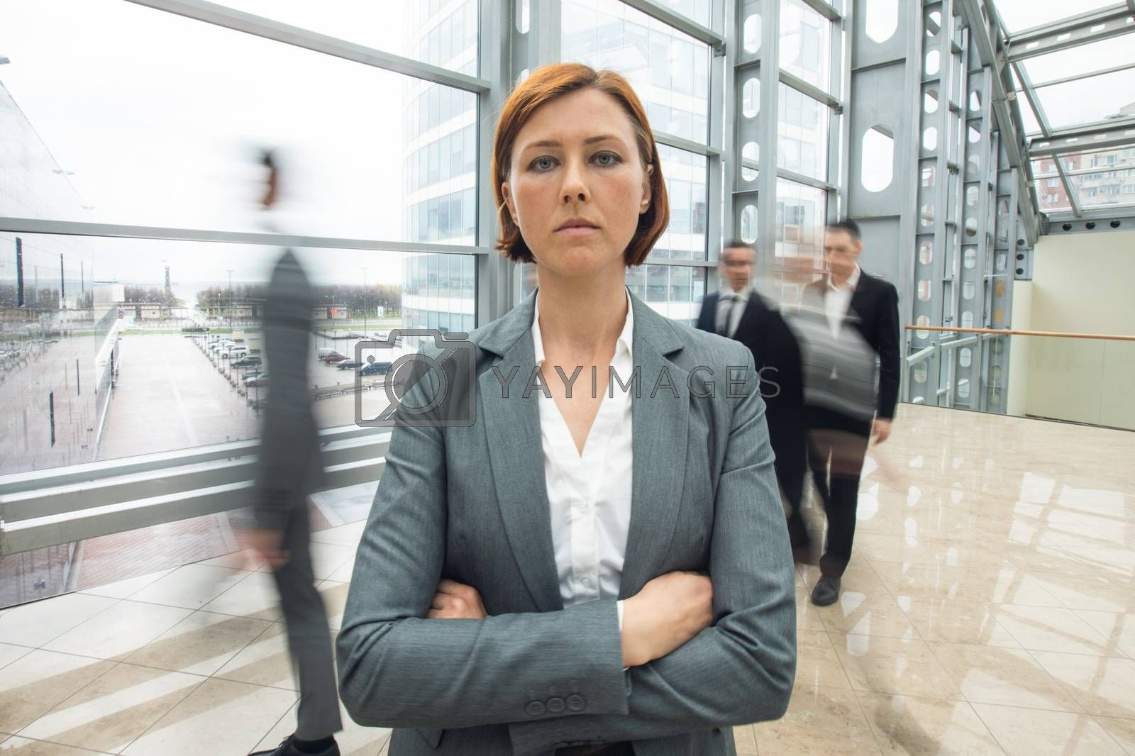 Young serious redhead businesswoman standing in a crowd with arms crossed