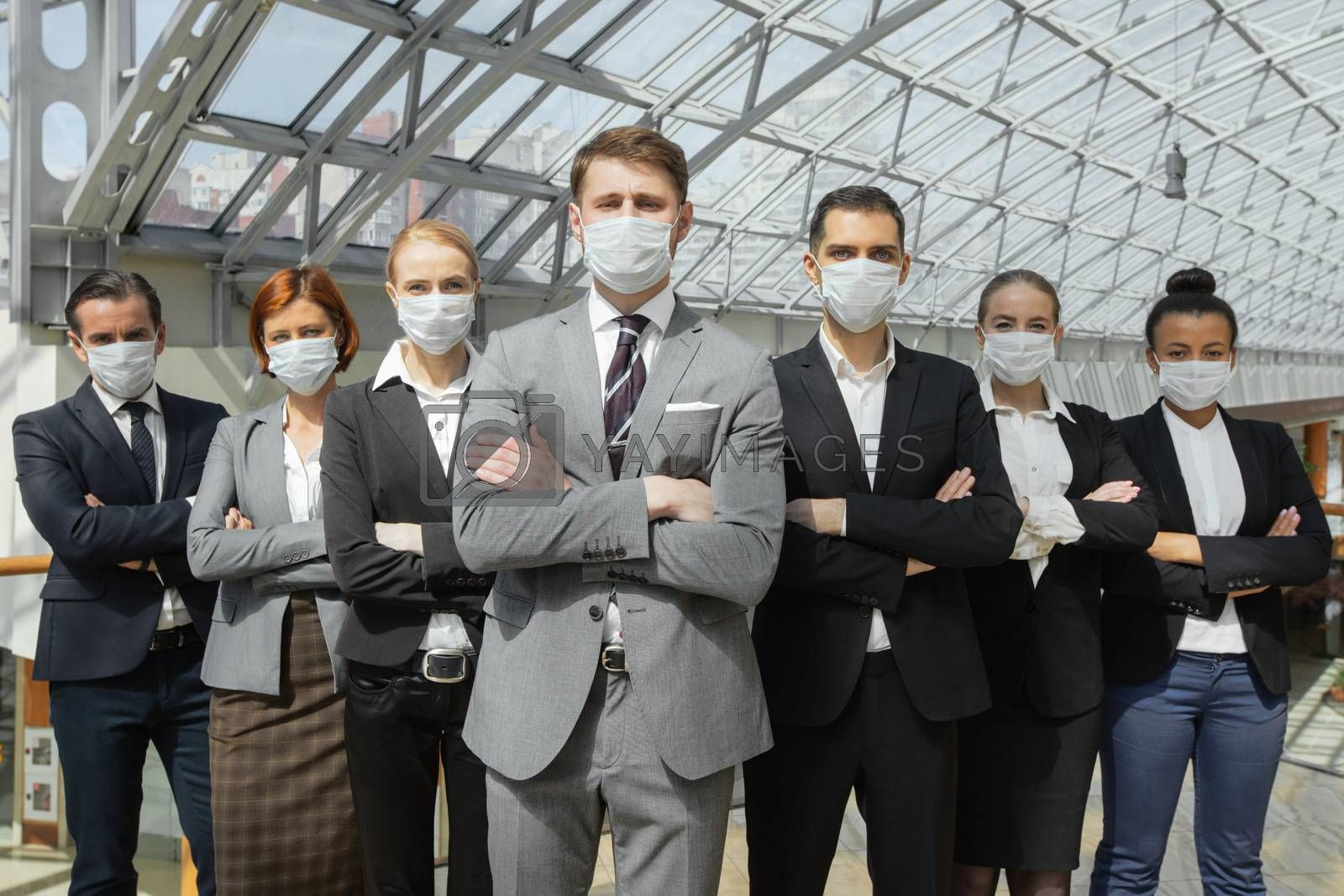 Business people wearing protective surgical masks and standing together with arms crossed, healthcare and covid-19 prevention concept