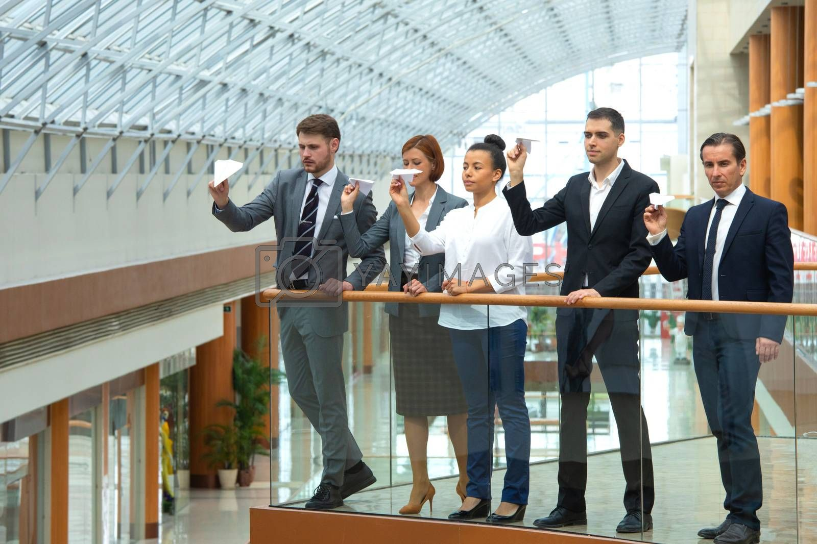 Team of business people throwing together paper planes in modern office building