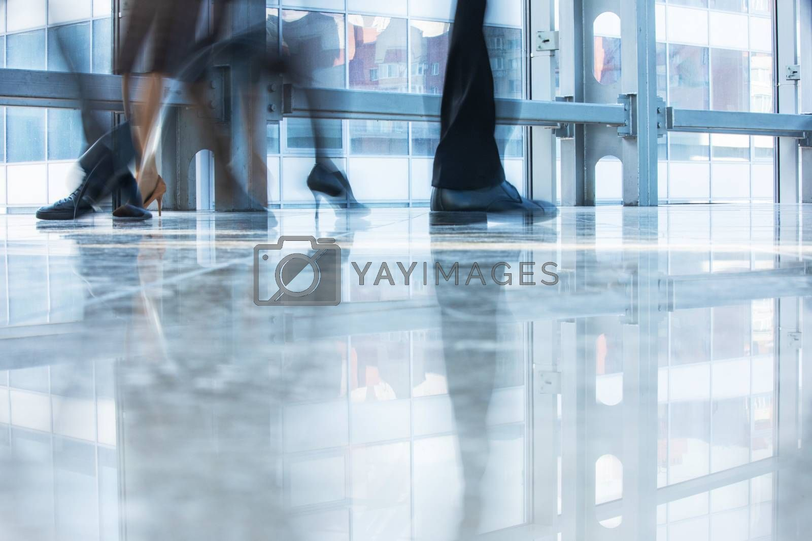 Blurred motion of business people walking inside modern office building wearing formal and high heel shoes of, business women, business man during rush hour