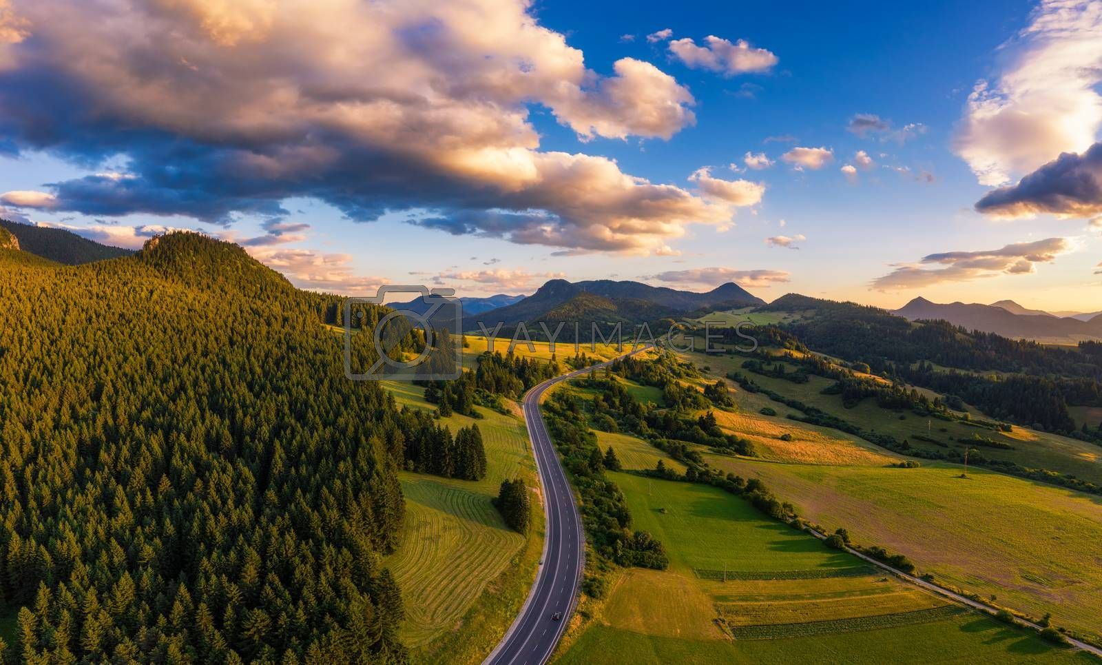 Aerial view of a road going through forests of the Liptov region in Slovakia at sunset.