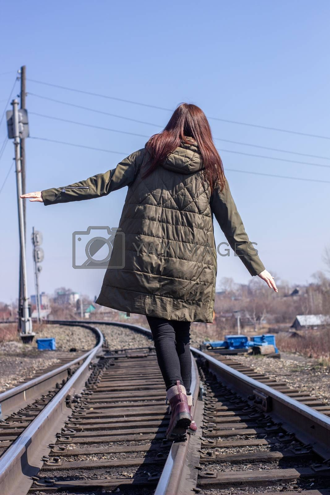 The girl is walking on the railway in front. Rear view