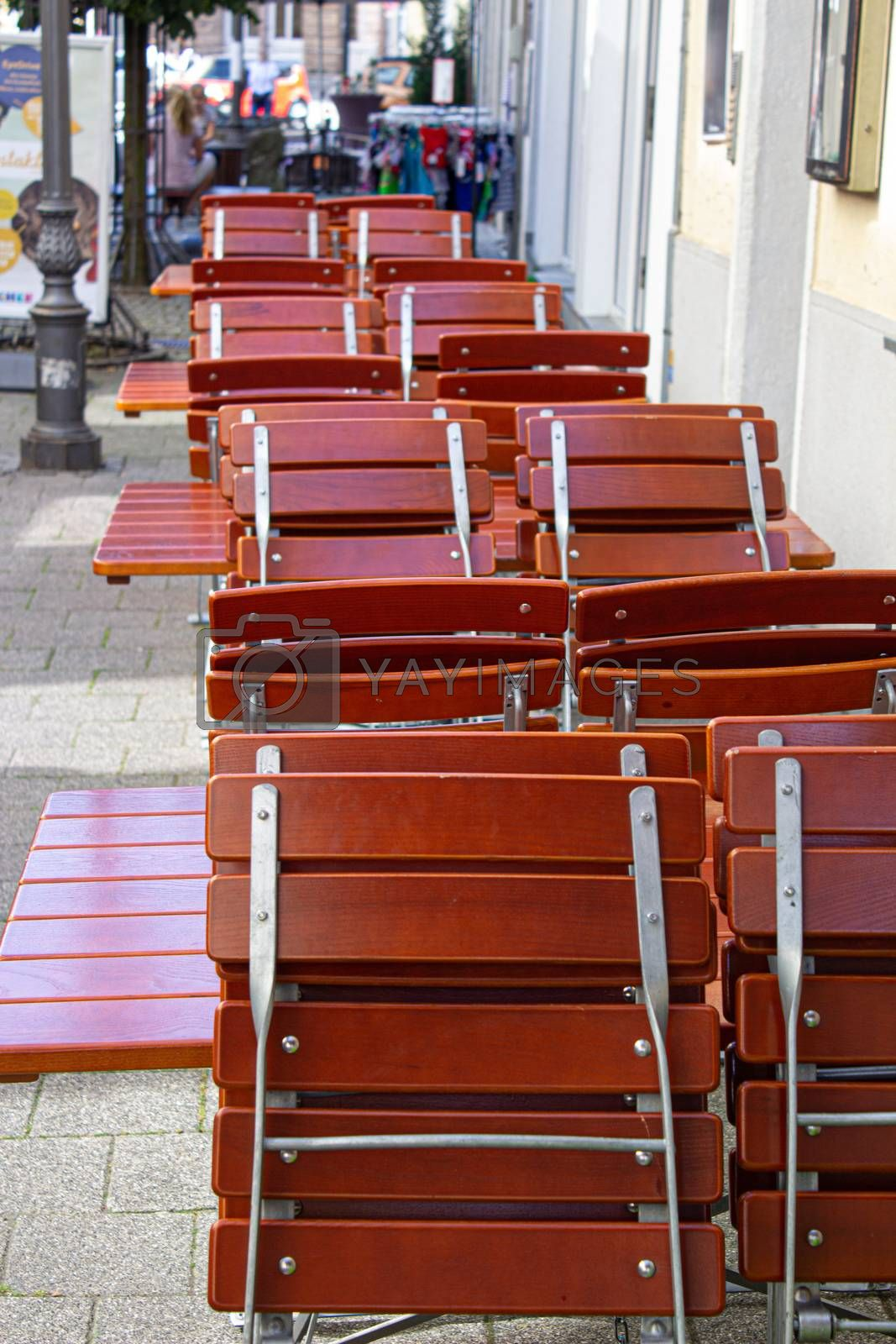 cafe street tables with chairs empty waiting for visitors arranges in structure red.