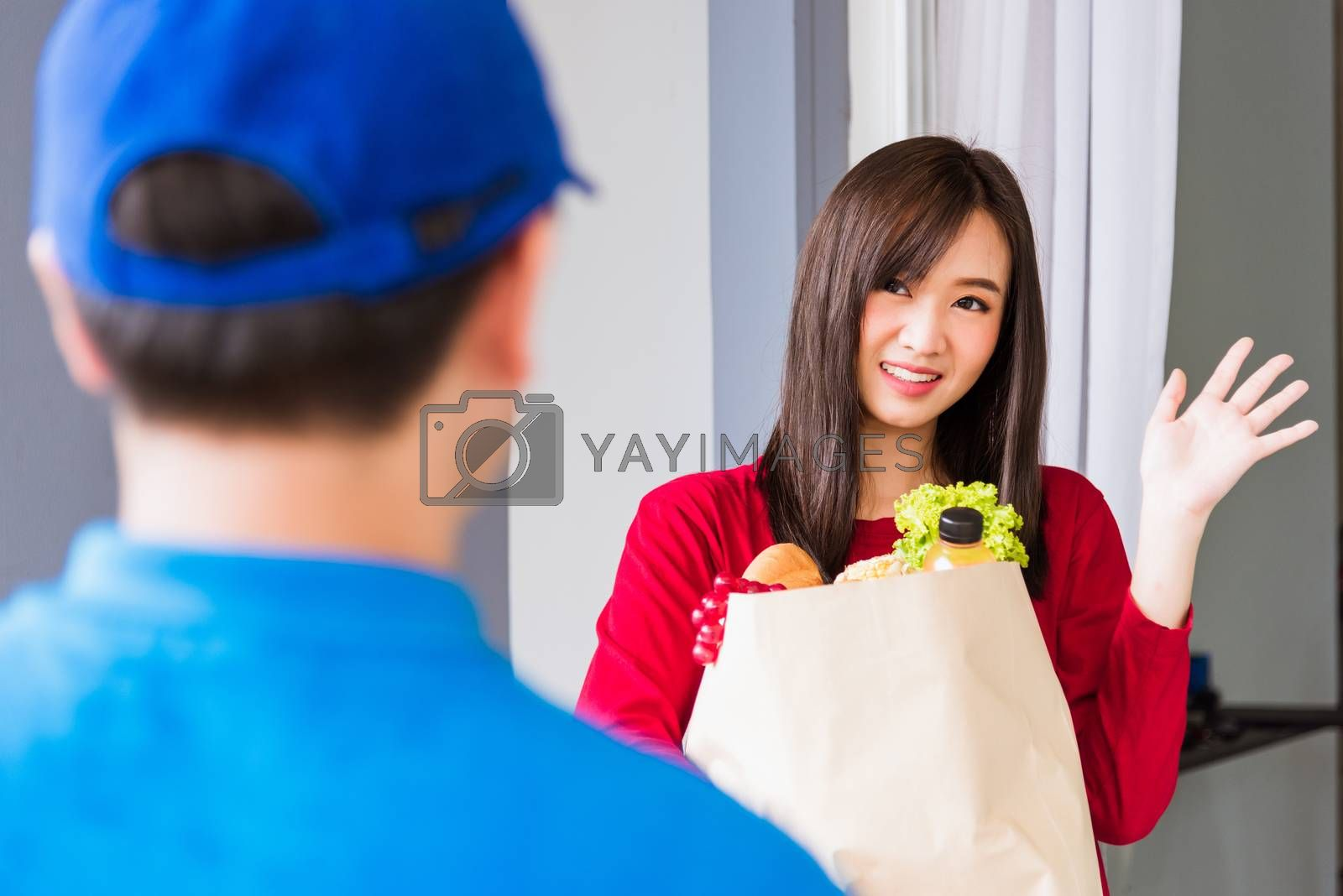 Delivery man making grocery service giving fresh vegetables in p by Sorapop