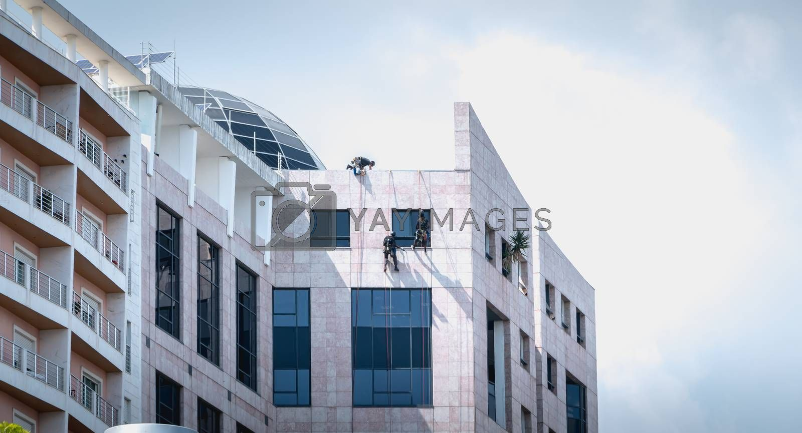Lisbon, Portugal - May 7, 2018 - Man washing windows climbing a building in Expo district on a spring day