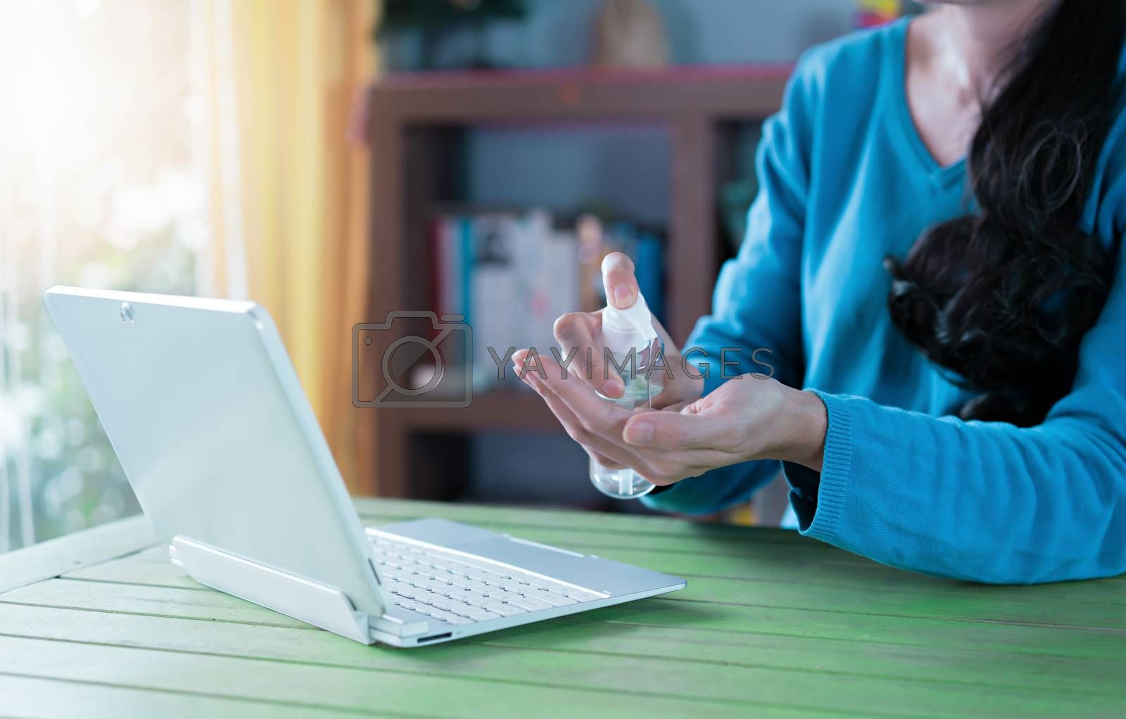 Woman working from home. Cleaning her hands with sanitizer gel.