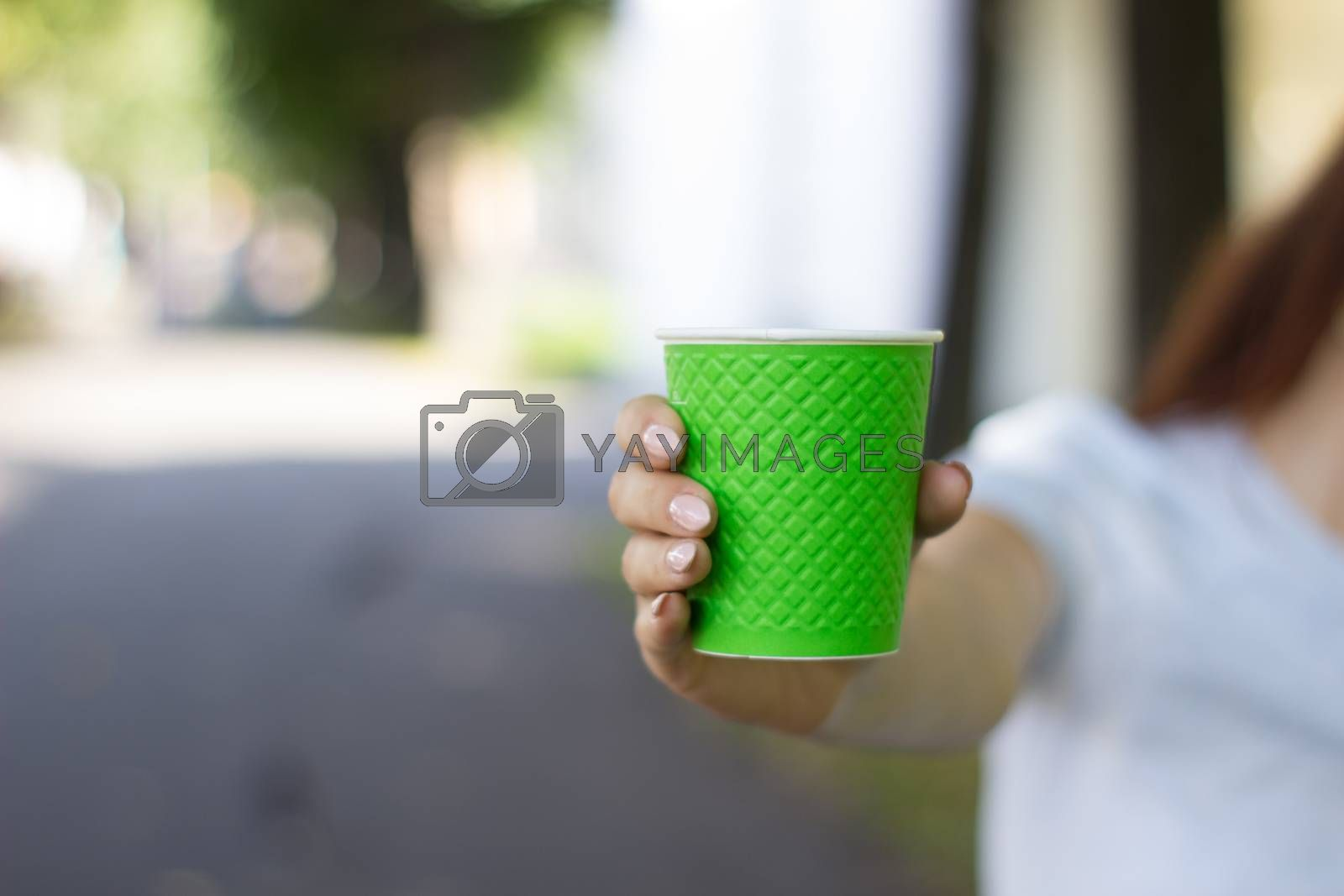 Mock up of cup coffee in woman's hand bright background for break, energy and strength, hot drink in paper cup. Tea or lemonade with ice, drink for business woman