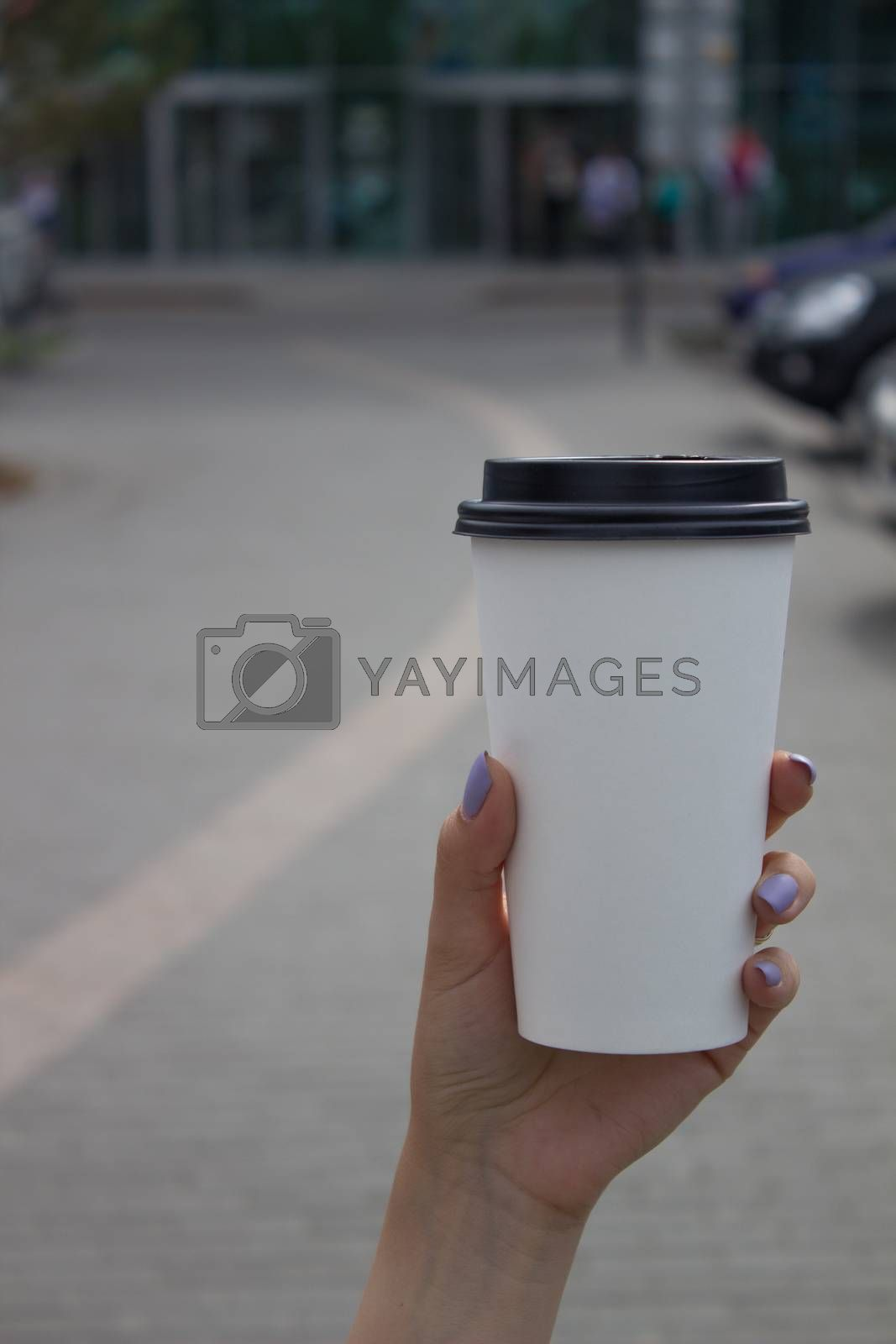 Breakfast and coffee theme: a woman's hand holding a white paper coffee Cup with a black plastic lid. Coffee advertising