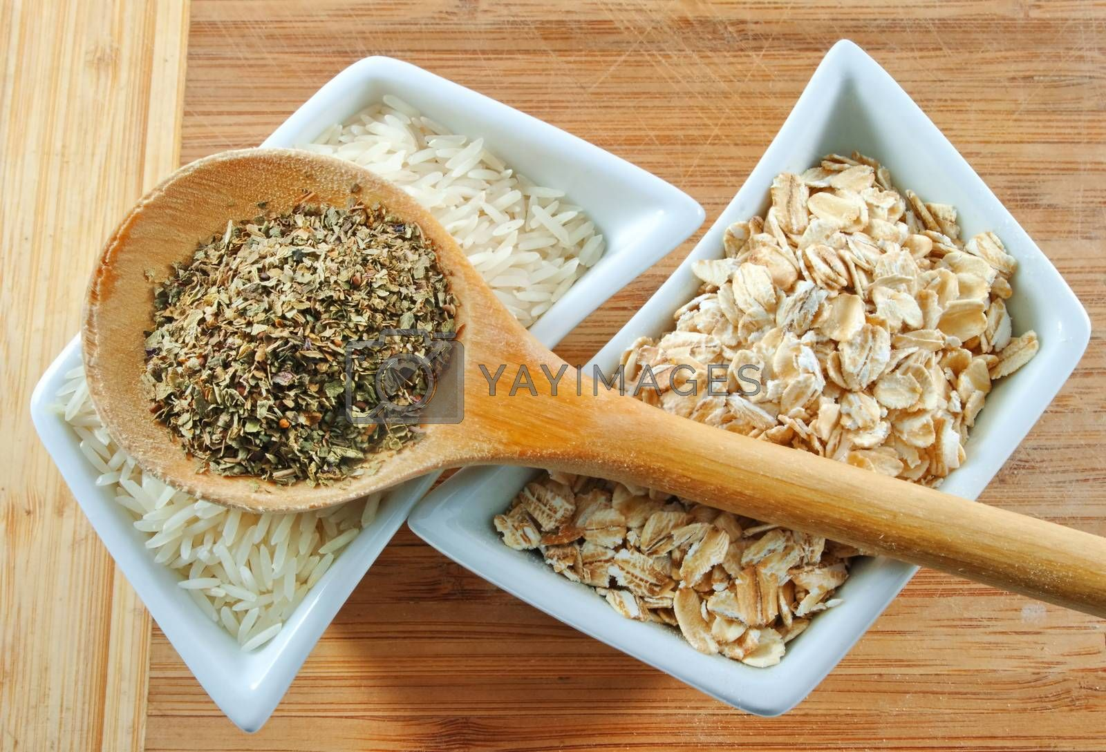 rice, oats and herbs on the wooden board