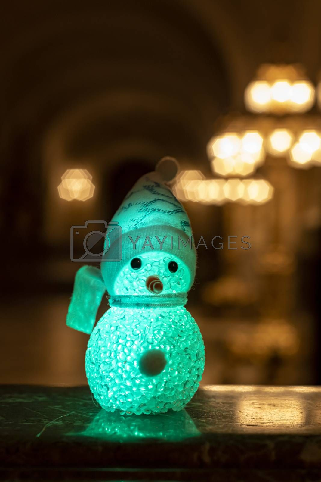 Little snowman wearing a rainbow scarf and hat against a golden light bokeh waiting for Christmas time and gifts