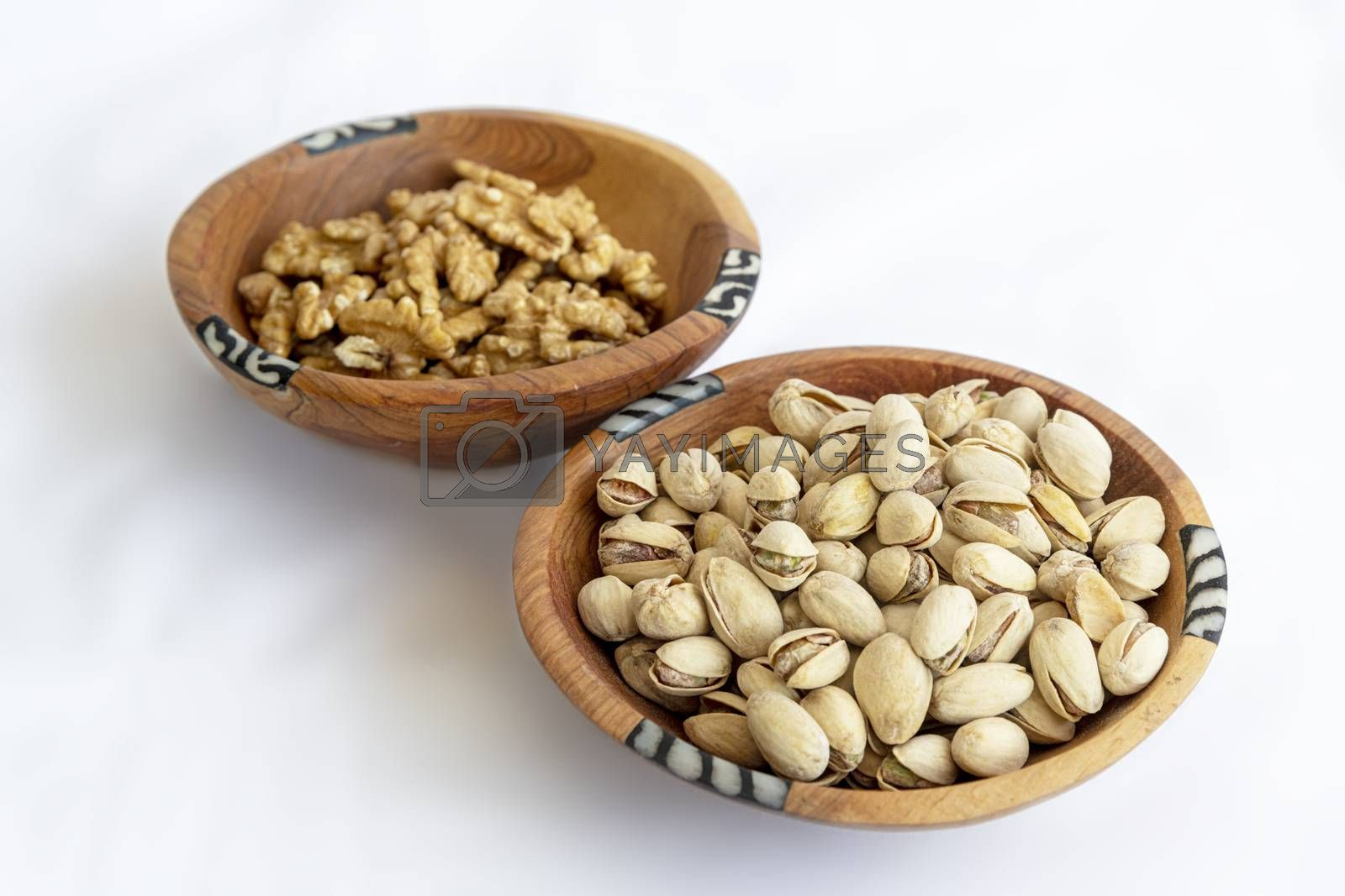Chestnuts and pistachios in wooden bol as appertiser with drinks against a white background