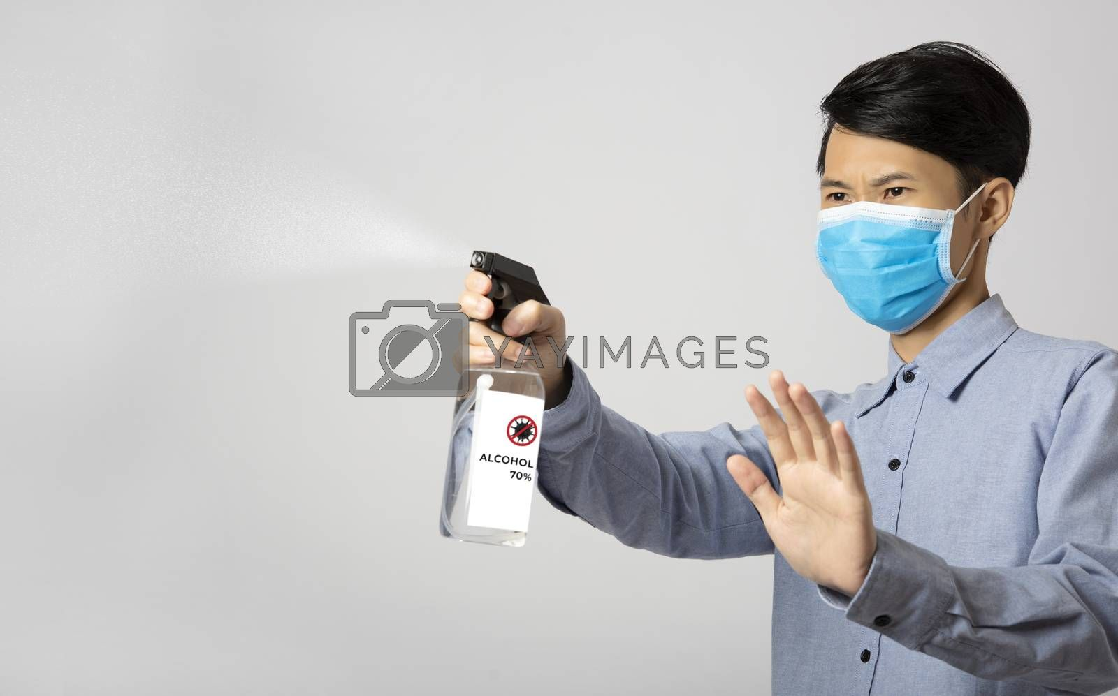Asia man using spray alcohol cleaning for protect anti virus bacteria.  Preventive measures against corona virus.