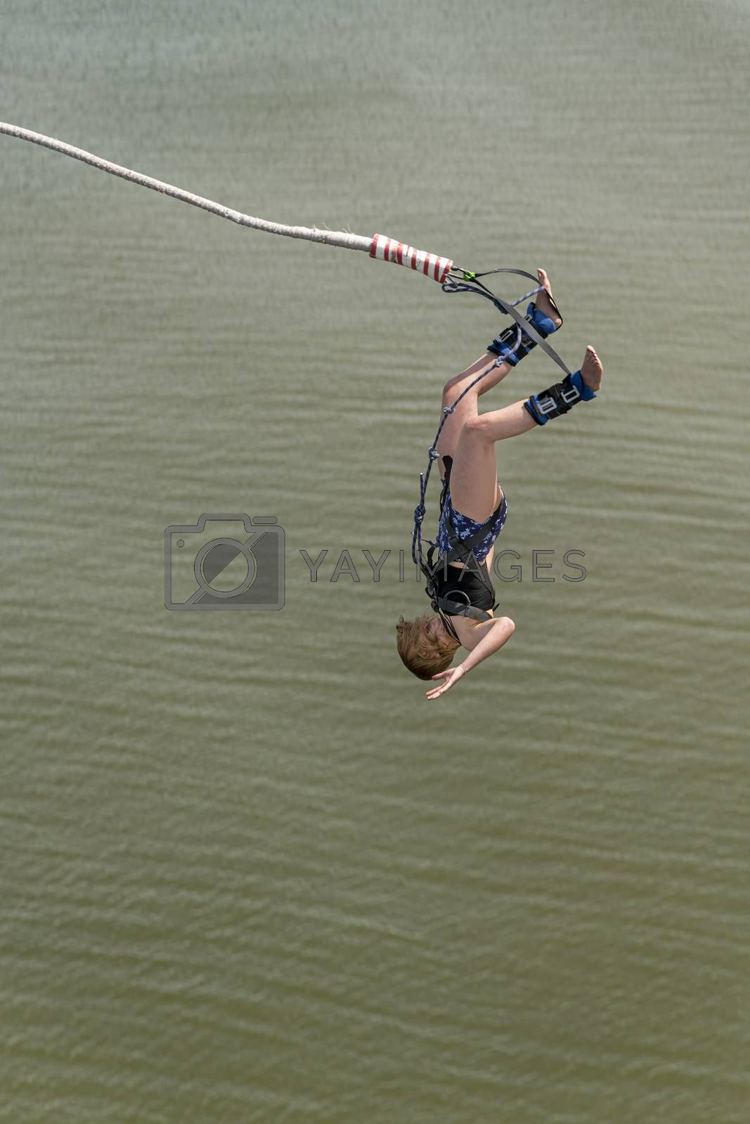 Bungee jumper jump from a platform hanging on the crane into the water against a pur blue spring sky of The Hague, Netherlands