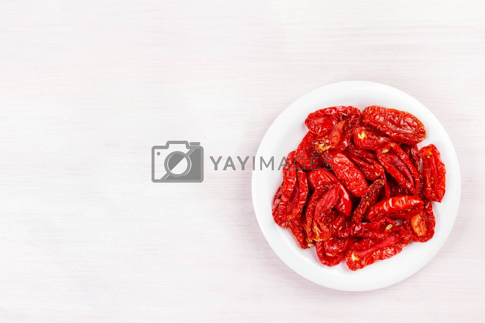 Sun dried tomatoes on bleached wooden table. Top view, flat lay