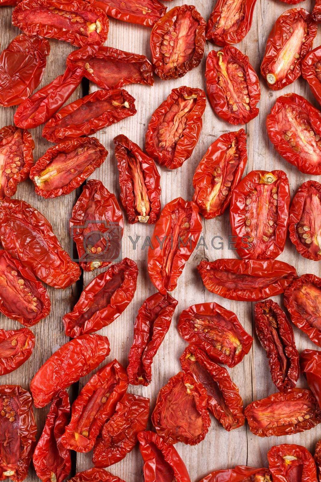 Sun dried tomatoes on wooden backdrop