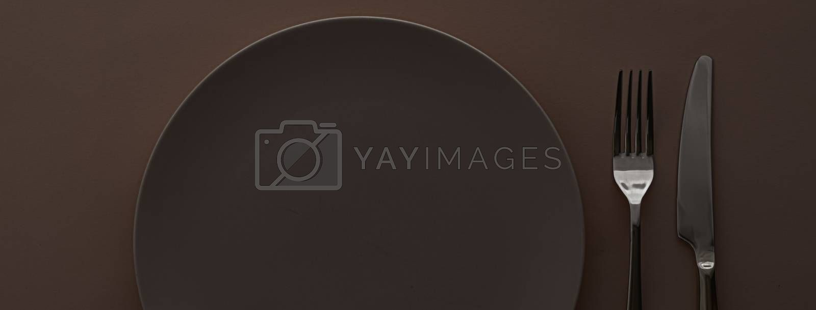Empty plate and cutlery as mockup set on dark brown background, top tableware for chef table decor and menu branding design