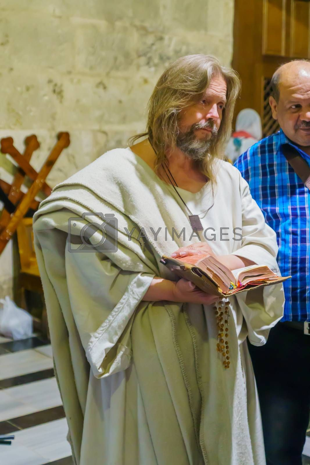 Jerusalem, Israel - April 6, 2018: Orthodox good Friday scene in the church of the holy sepulcher, with a pilgrim dress like Jesus. The old city of Jerusalem, Israel