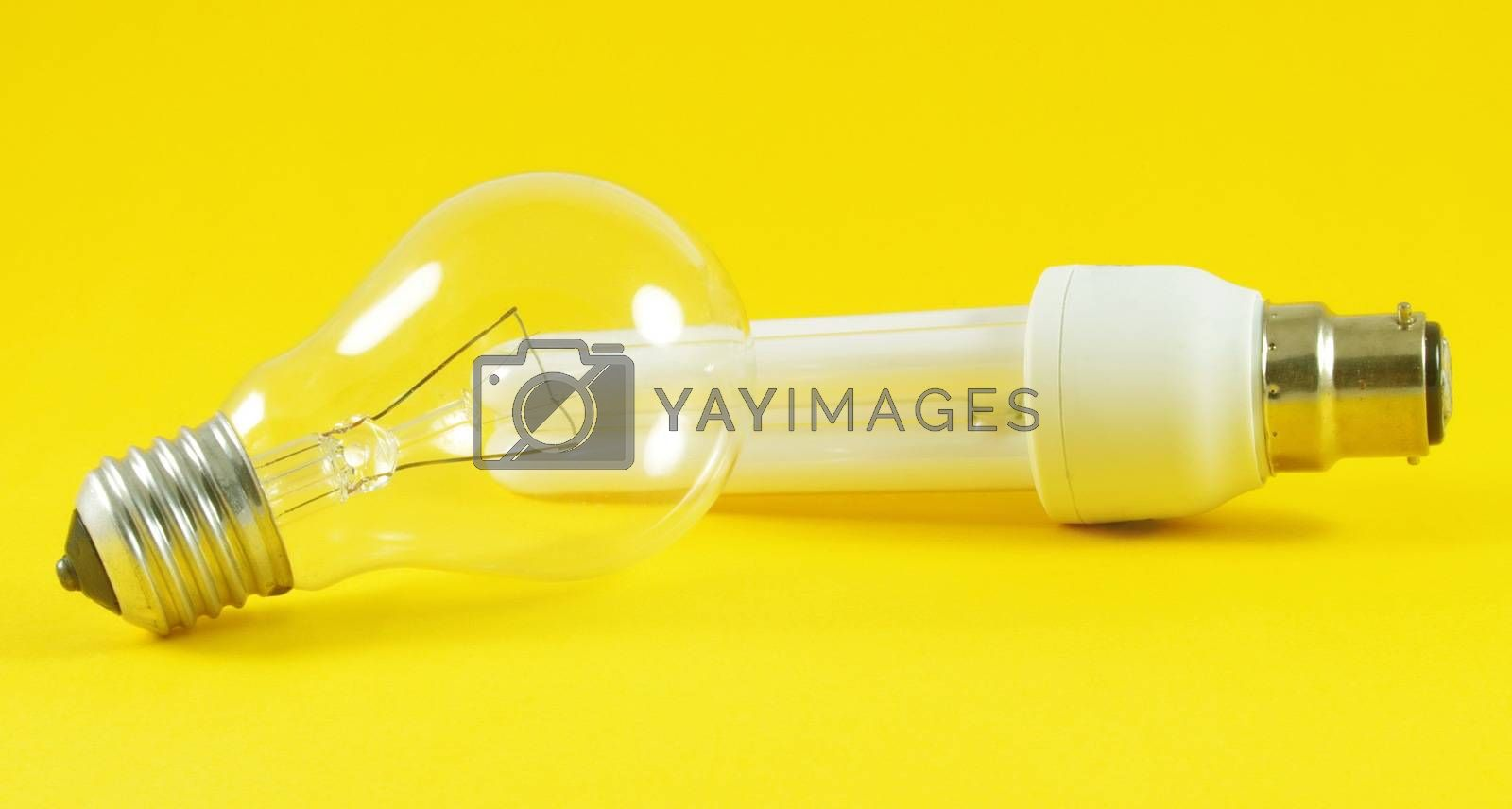 Economic and regular light bulbs over yellow background