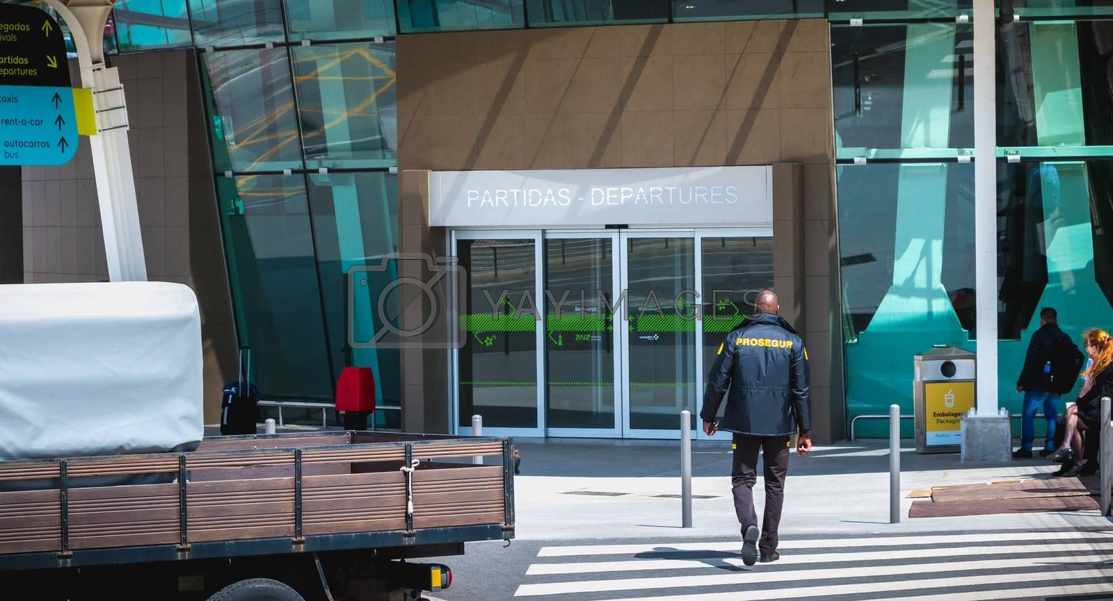 Faro, Portugal - May 3, 2018: Security guard supervising the entrance of Faro International Airport on a spring day