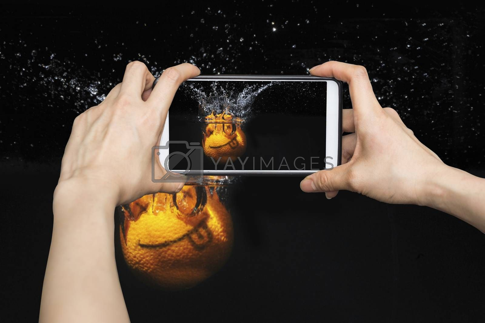 Taking pictures on mobile smart phone Smile orange with splashes of water on a black background
