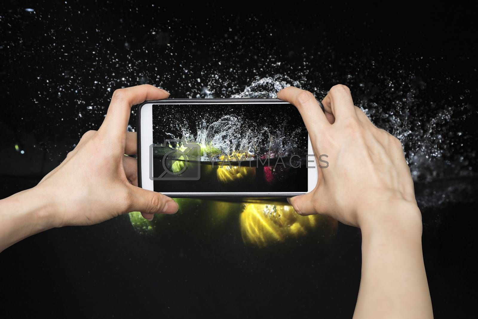 Taking pictures on mobile smart phone in Splashing fruit on water. Fresh Fruit in black background