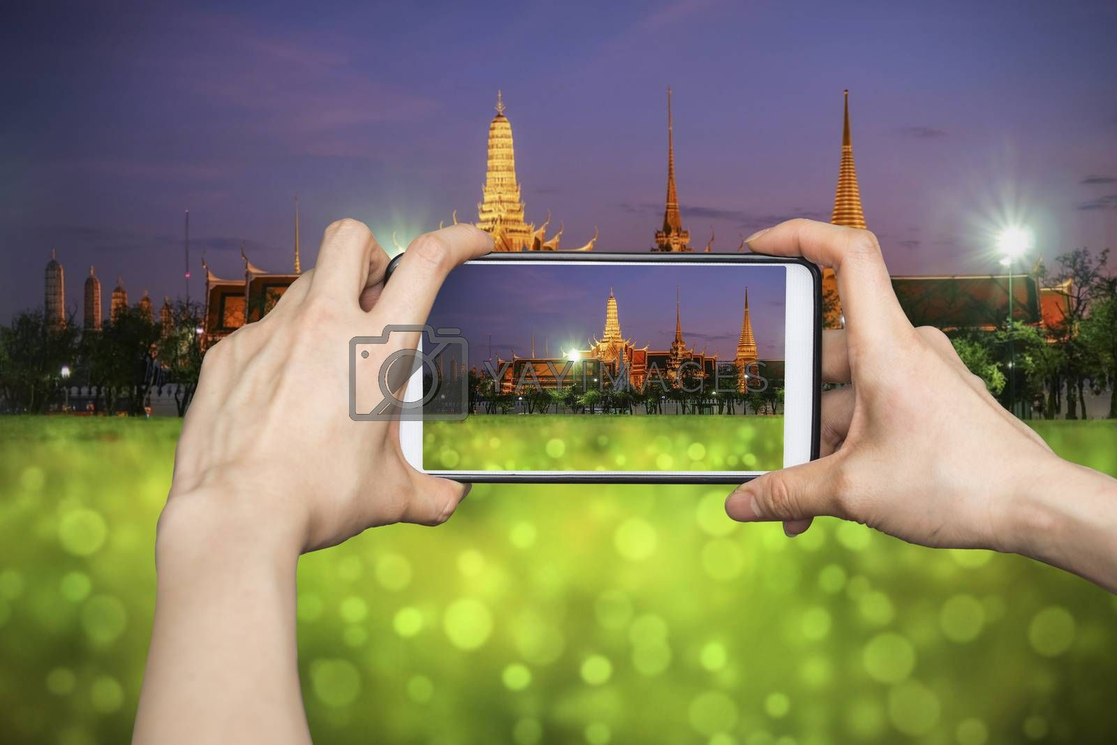 Taking pictures on mobile smart phone in Wat Phra Kaew (The Emerald Buddha) night view in Thailand