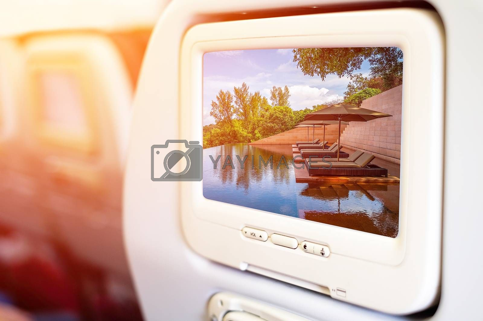 Aircraft monitor in passenger seat on beach pool background