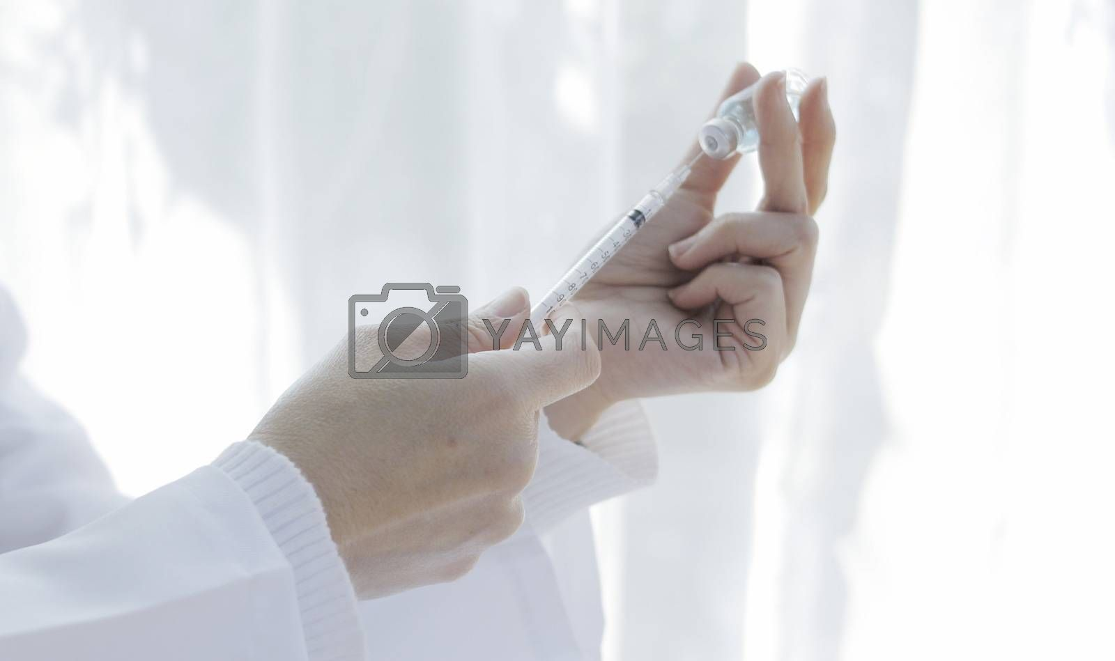 The doctor's hand has a vaccine bottle. Covid 19 virus concept