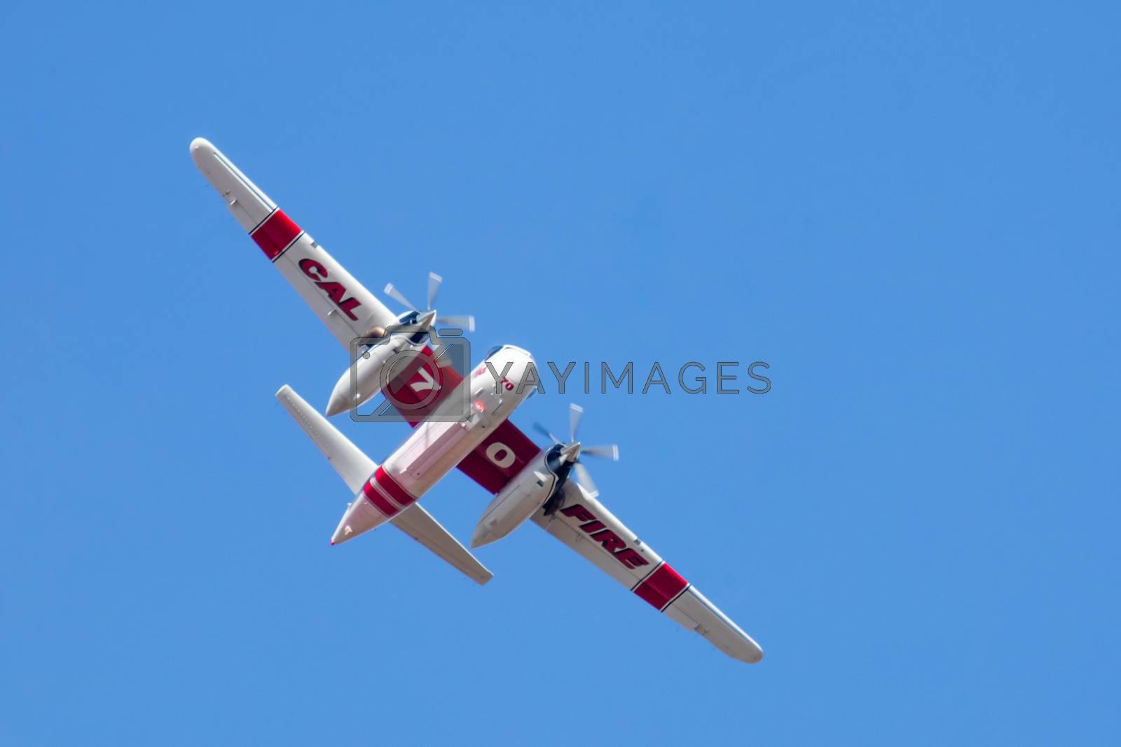 Winchester, CA USA - June 14, 2020: Cal Fire aircraft preparingto drop fire retardant on a dry hilltop wildfire near Winchester, California.