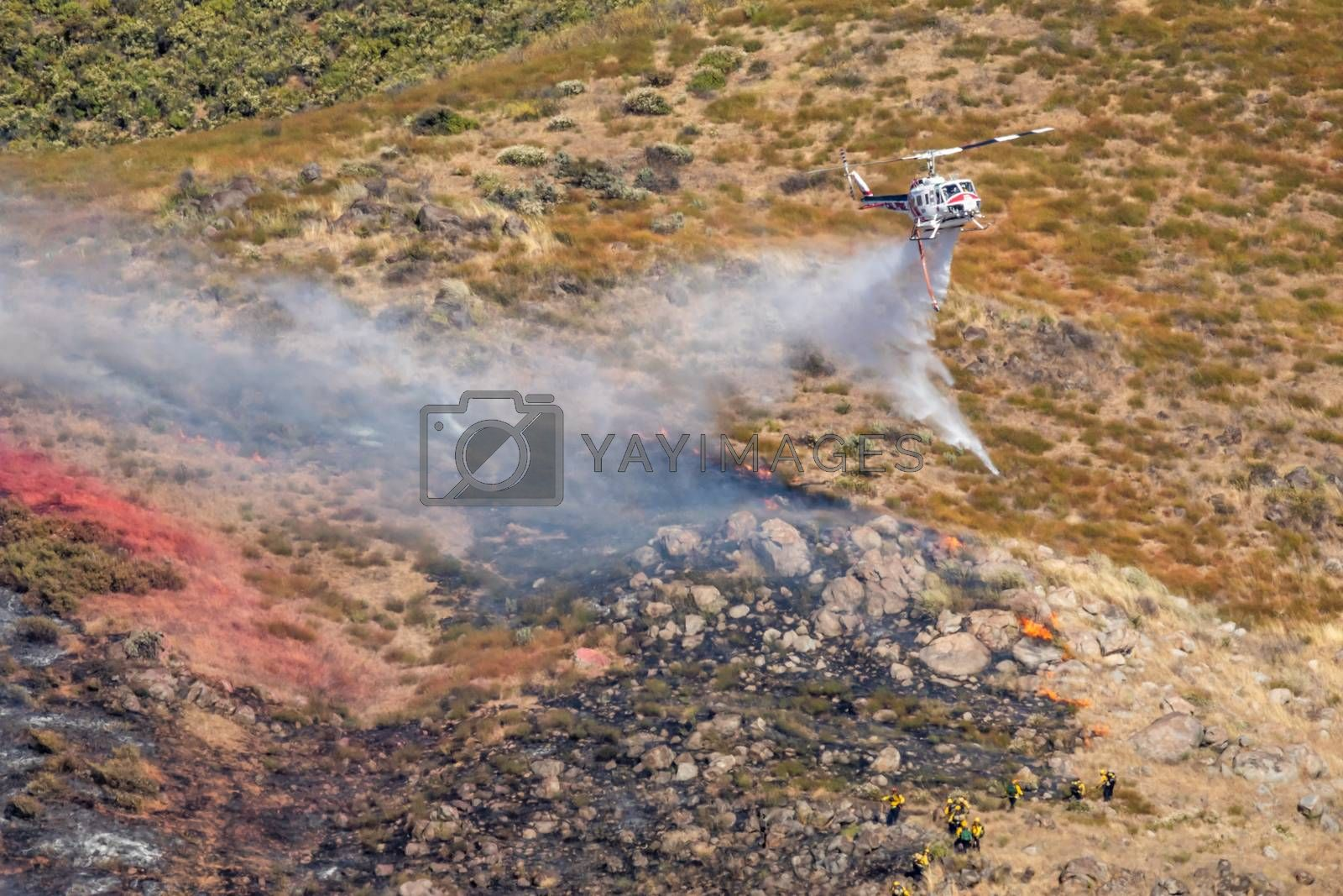 Winchester, CA USA - June 14, 2020: Cal Fire helicopter drops water on a dry hilltop wildfire near Winchester, California.