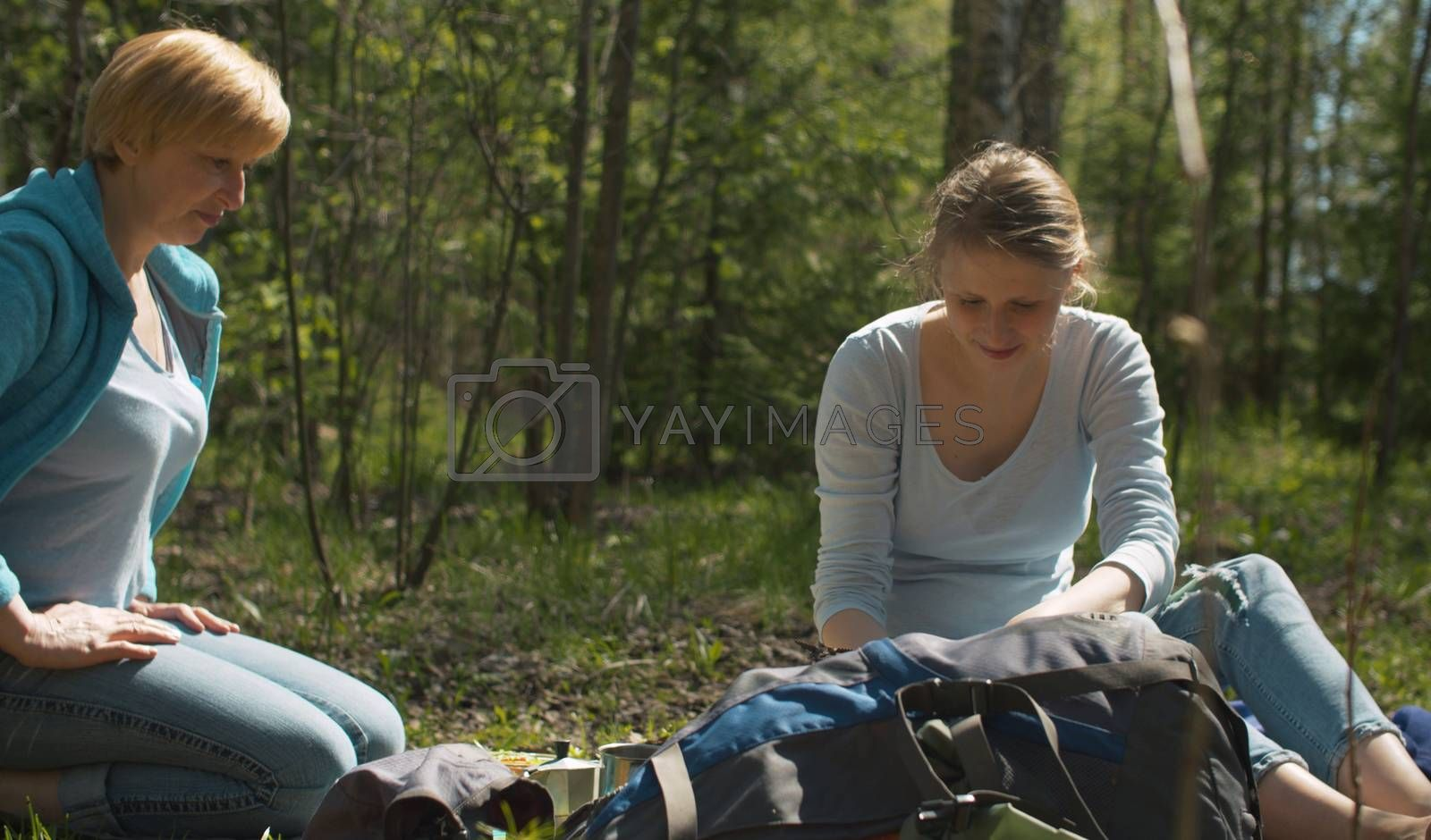 Snack during trekking. Two women sitting on the grass in the forest. They take out a italian espresso maker and a lunch box from a backpack.