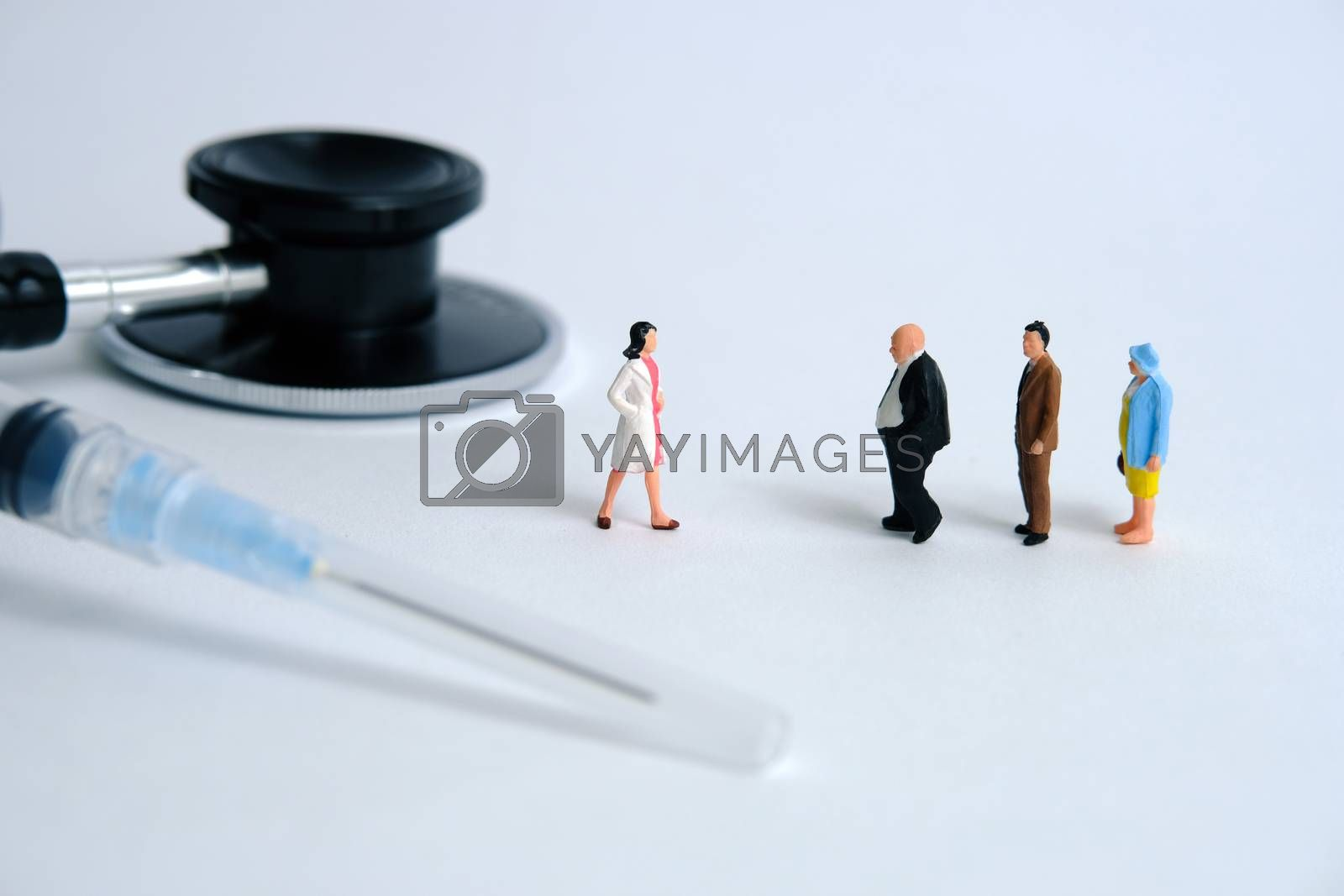 Pandemic coronavirus conceptual miniature people photography – a group of people line up in line for a health check. Image Photo