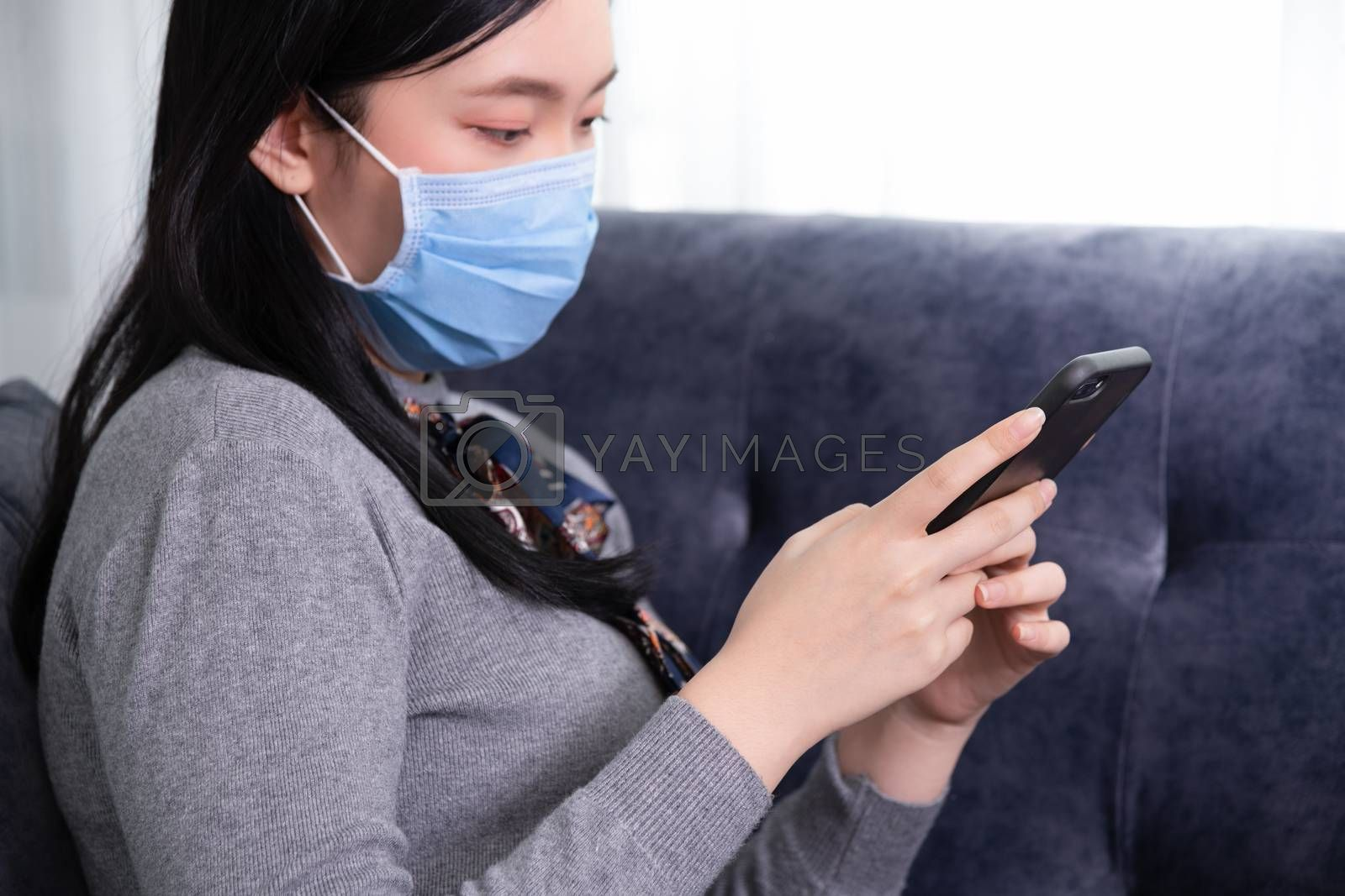 Close up of a female using mobile smart phone and wearing wearing protective mask