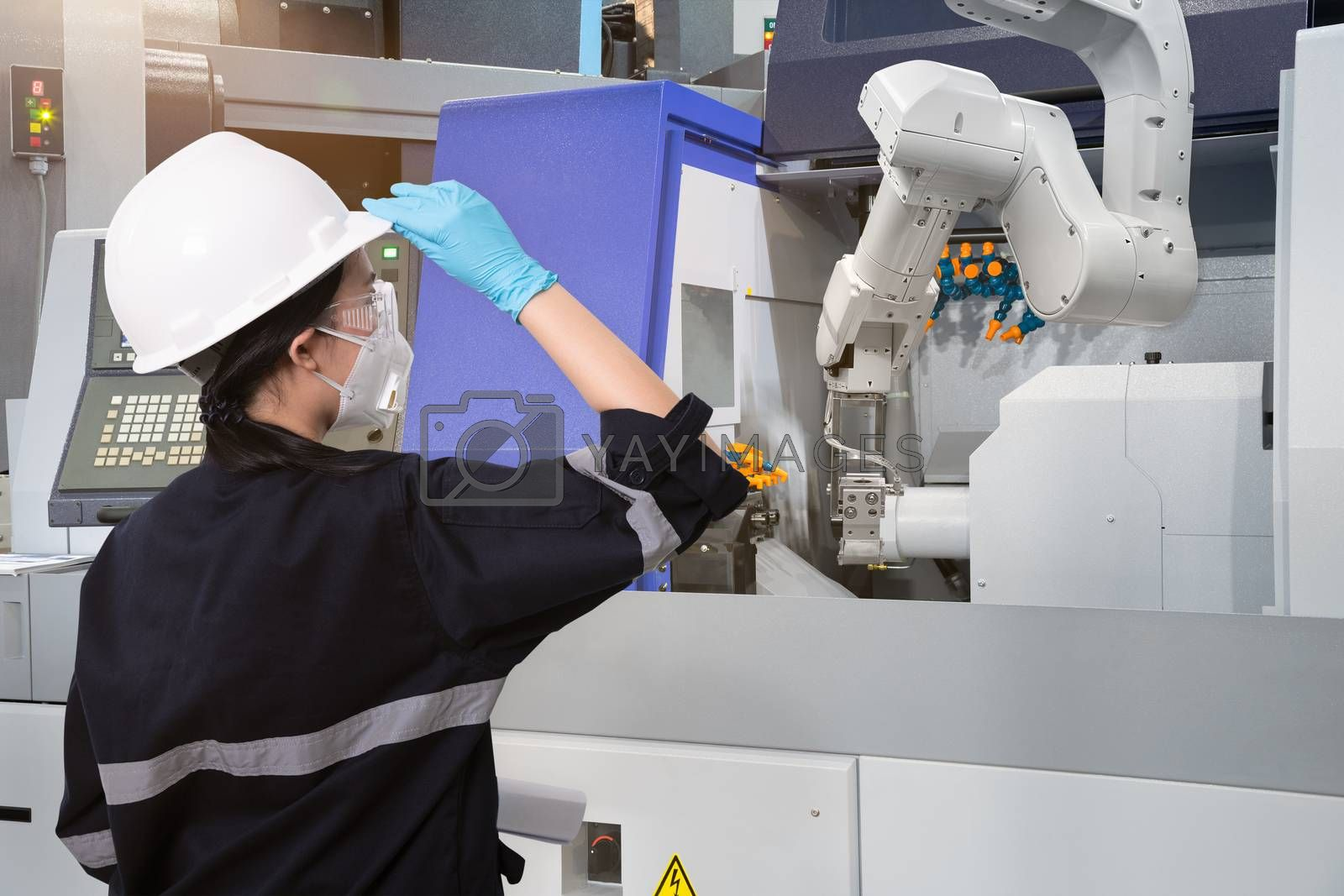 Female engineer wearing protective mask and glove to protect against Covid-19 and looking at robot CNC machine in smart factor