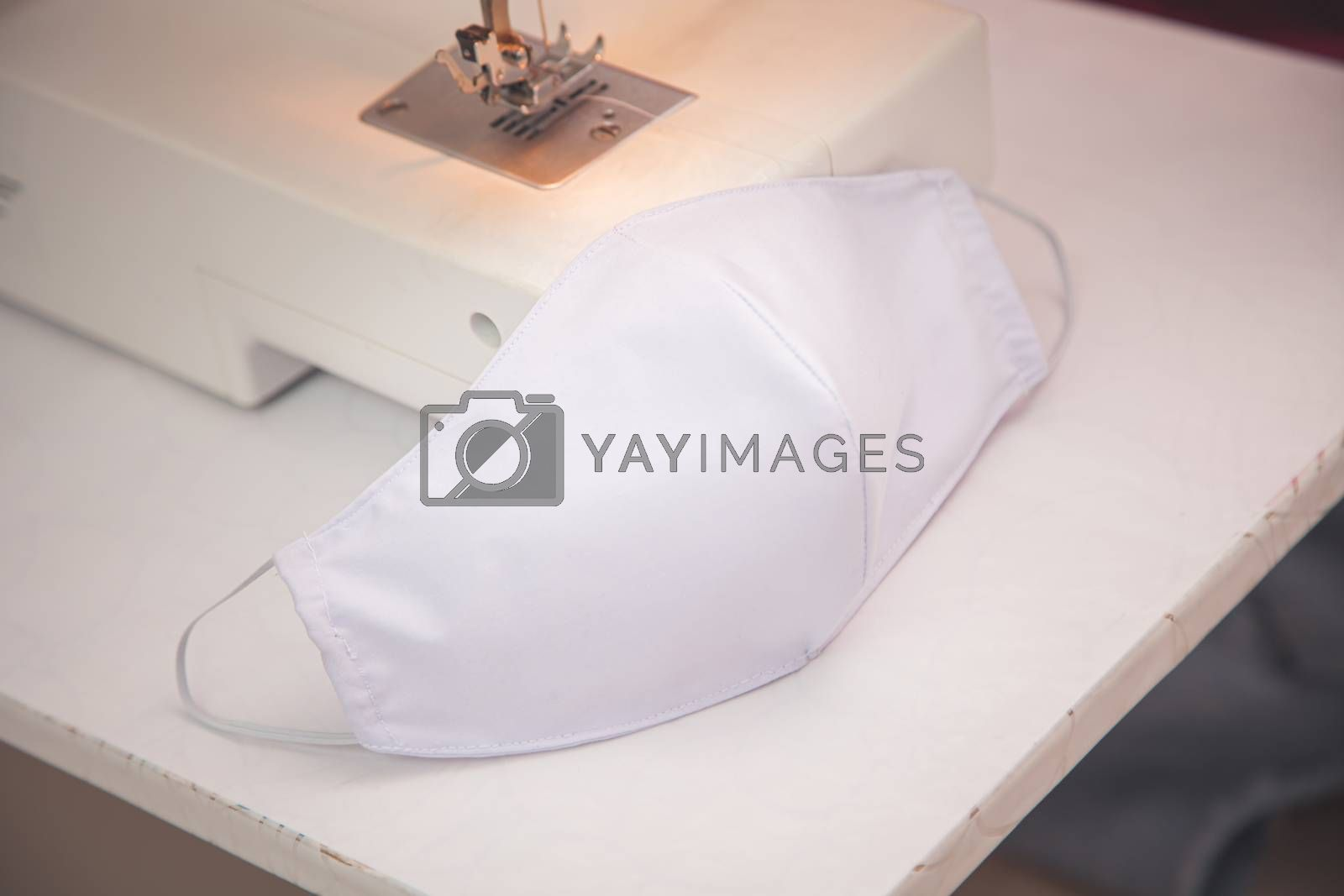 Woman making to sew the face fabrics medical mask with sewing machine during quarantine at home. Home made diy protective anti-virus mask against virus infection. Epidemic outbreak COVID-19 concept
