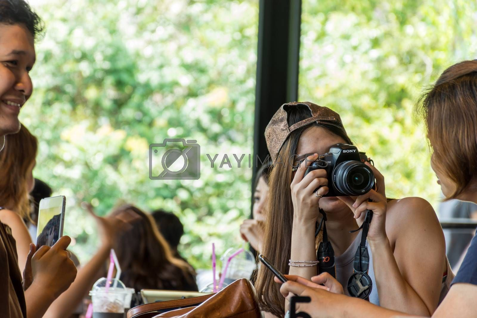 Chanthaburi, Thailand - May 6, 2016 : Unidentified asia woman take a photo by her camera at restaurant or cafe when travel with her best friends