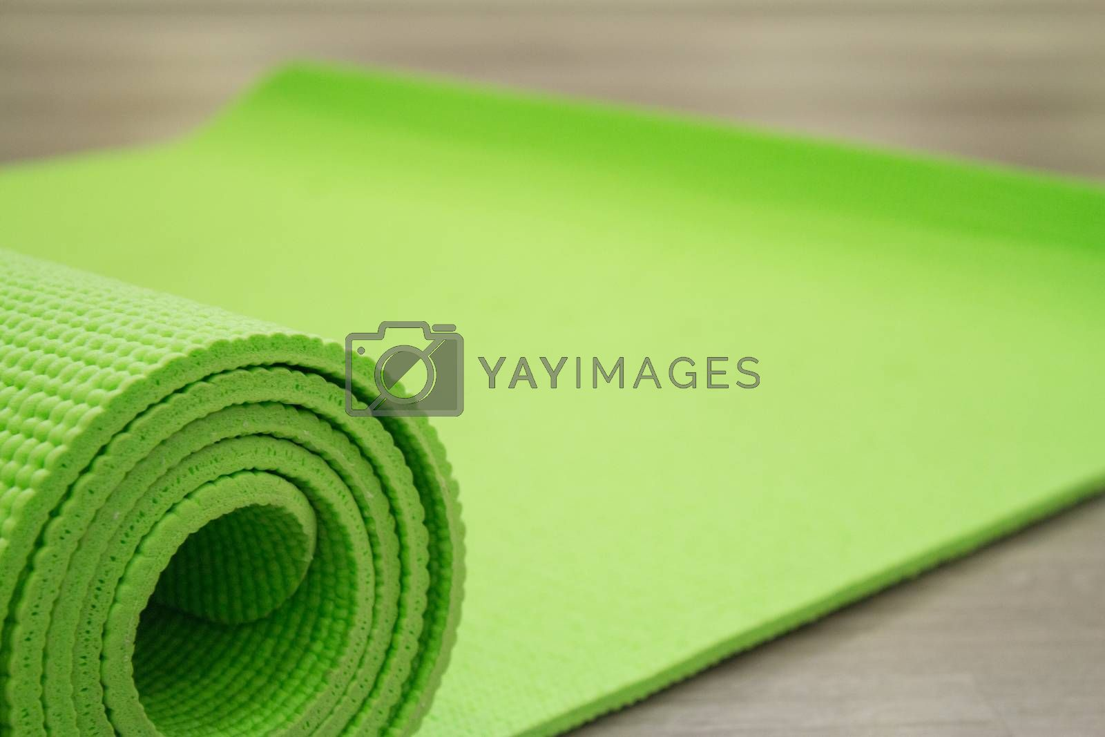 Green yoga mat unrolled on the wooden floor.