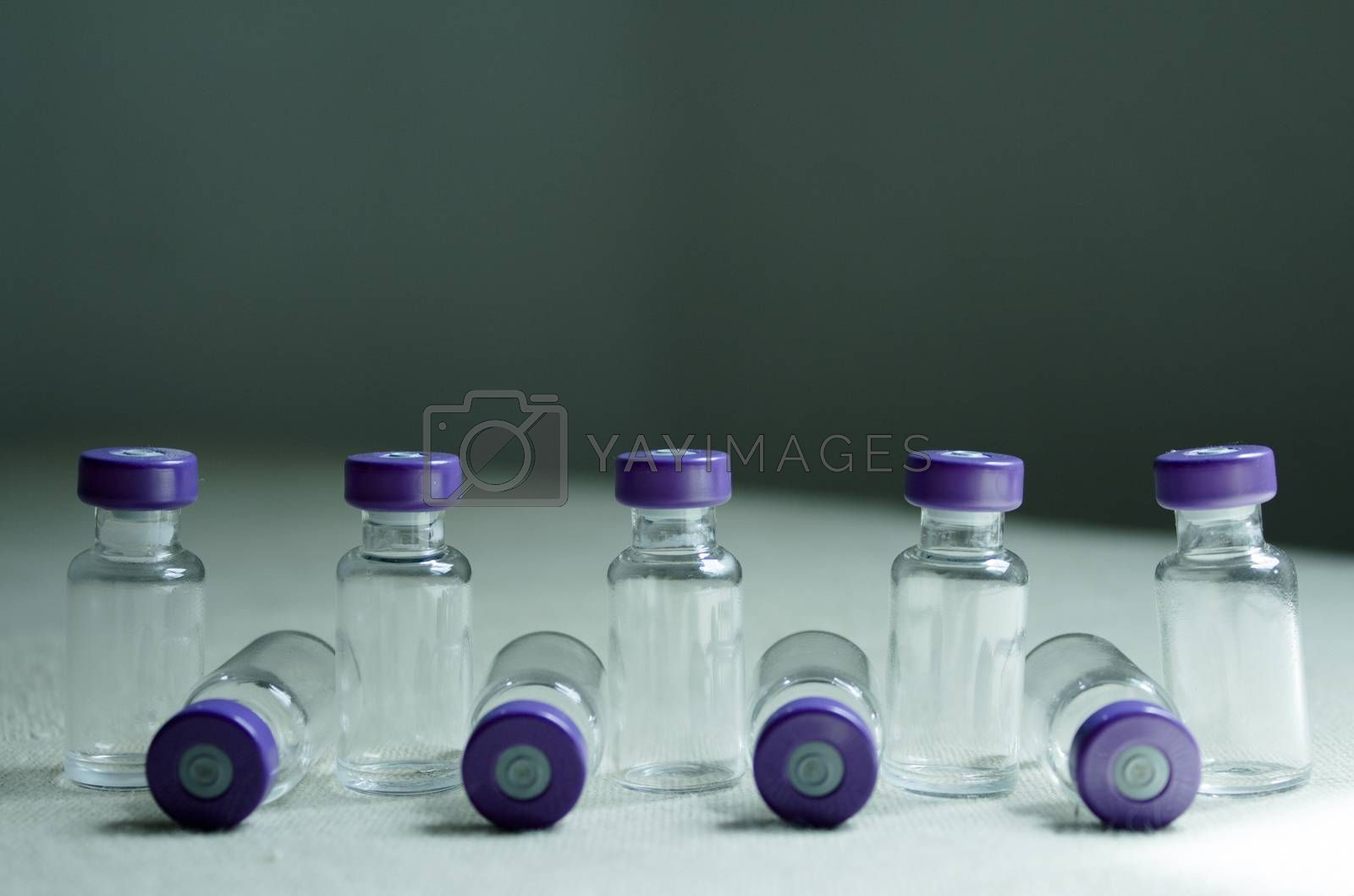 Several empty vials placed online. Greenish background.