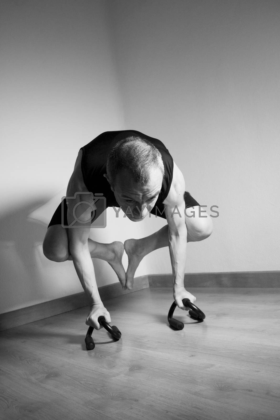 Man performing crow motion in yoga