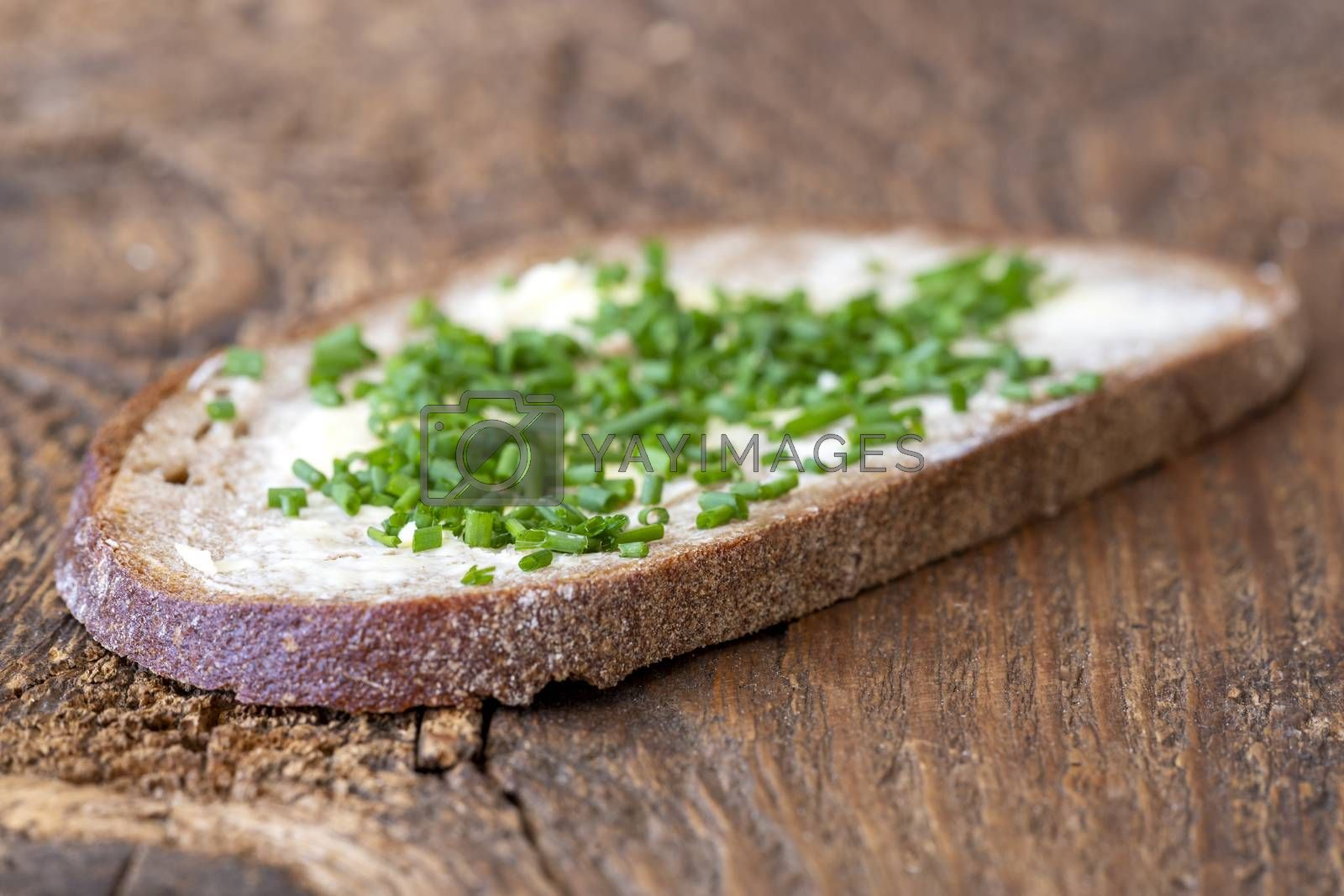 bread with butter and chives on wood