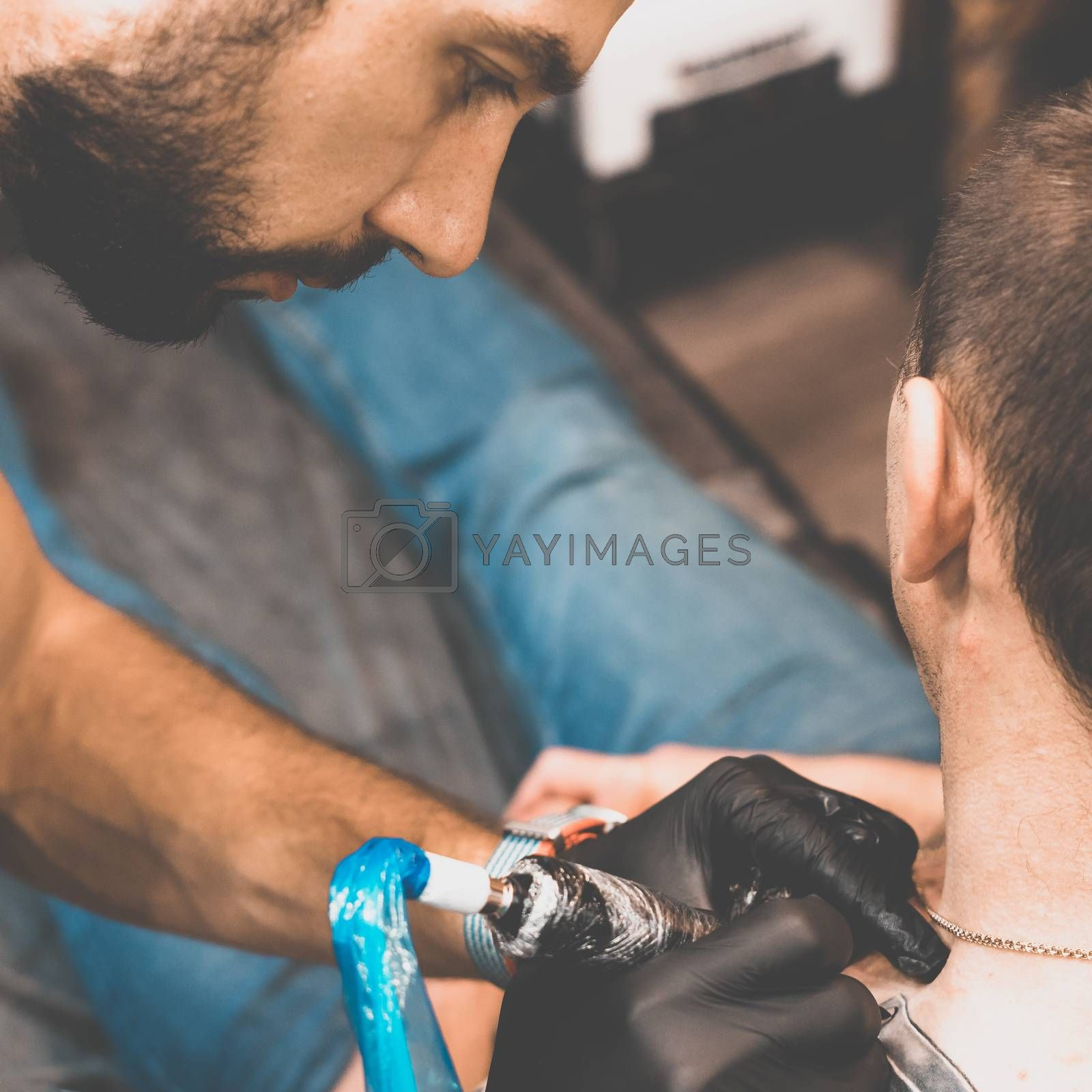 Tattoo salon. The tattoo master is tattooing a man on his shoulder. Tattoo machine, safety and hygiene at work. Close-up, tinted, tattooist.