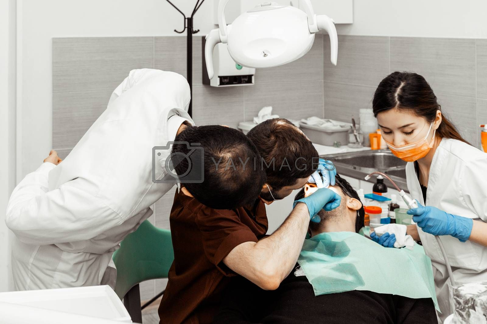 Two dentists treat a patient. Professional uniform and equipment of a dentist. Healthcare Equipping a doctors workplace. Dentistry